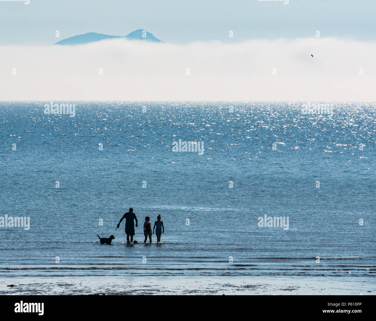 east-lothian-scotland-united-kingdom-27th-june-2018-uk-weather-sea-fog-or-haar-in-the-firth-of-forth-coast-created-a-haze-a-family-enjoys-an-evening-dip-to-cool-down-in-the-sea-with-the-distinctive-outline-of-arthurs-seat-in-edinburgh-just-visible-through-the-fog-P610FP.jpg