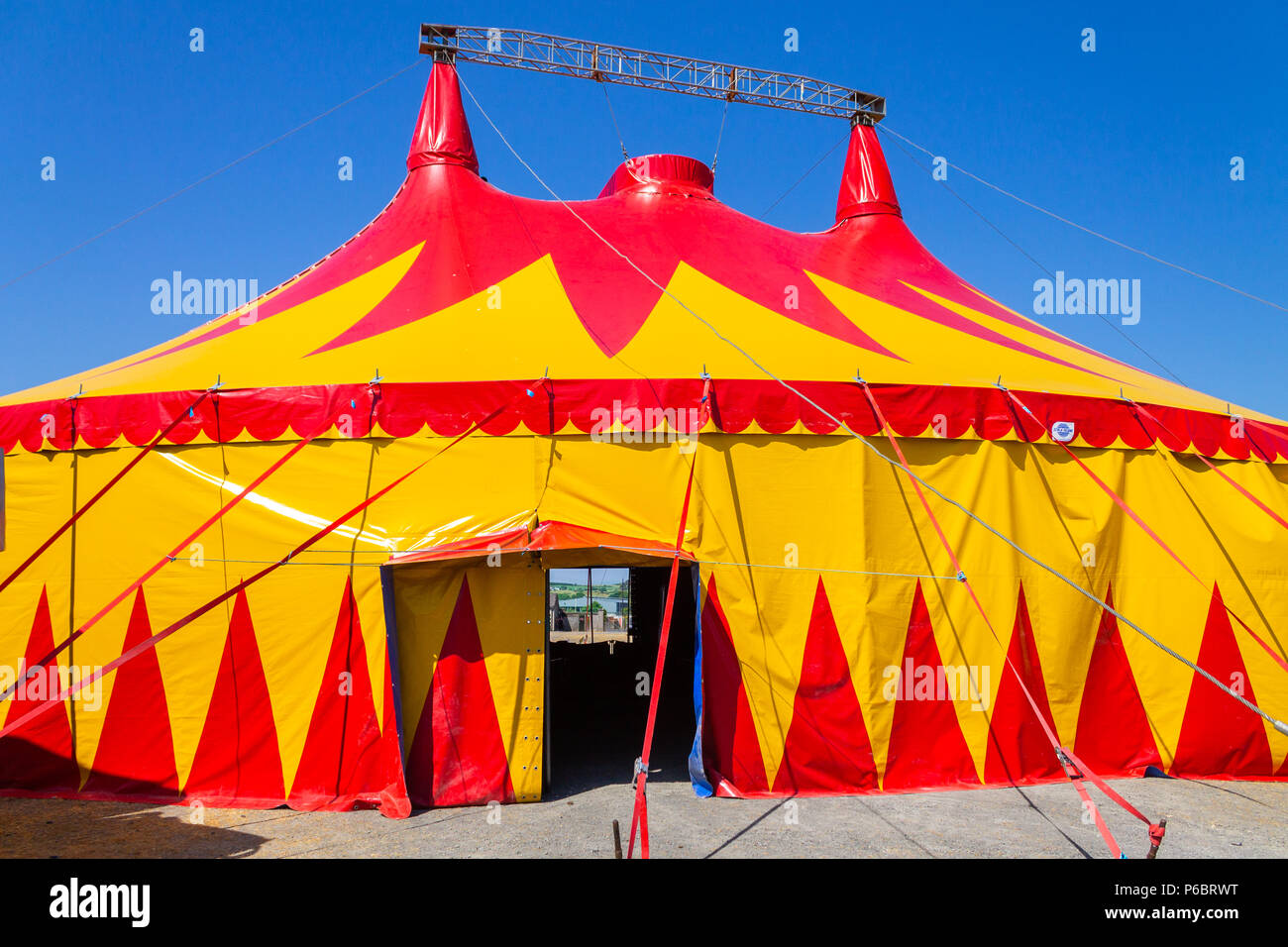 circus-tent-or-big-top-with-red-and-yellow-design-standing-out-against-a-clear-blue-sky-P6BRWT.jpg
