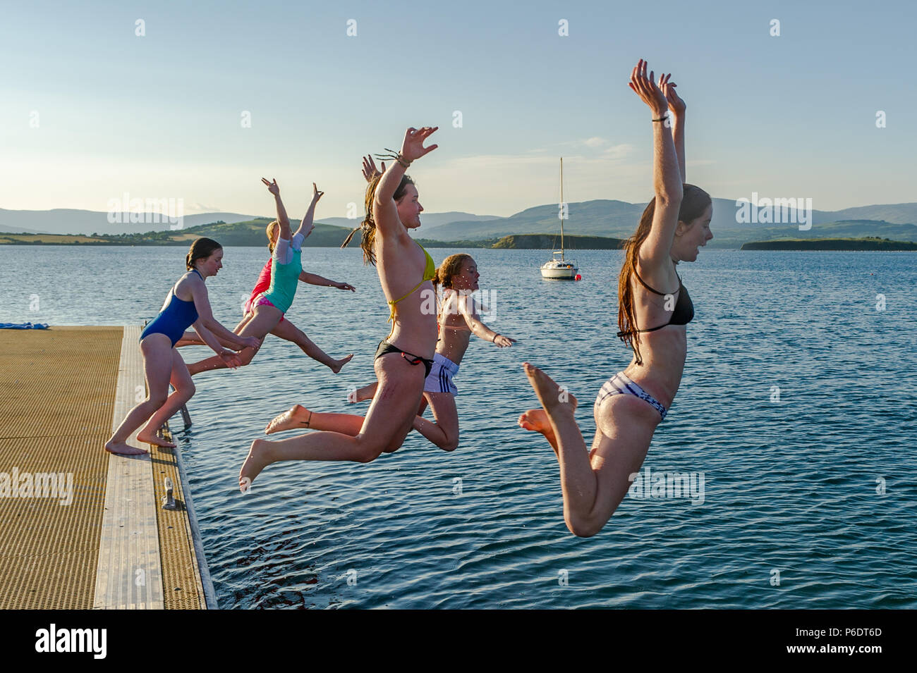 bantry-west-cork-ireland-29th-june-2018-after-a-scorchingly-hot-day-during-the-current-heatwave-a-group-of-young-girls-jump-into-the-sea-from-a-pontoon-as-the-sun-goes-down-in-bantry-the-rest-of-the-weekend-will-be-cooler-than-previous-days-with-rain-forecast-for-next-week-credit-andy-gibsonalamy-live-news-P6DT6D.jpg