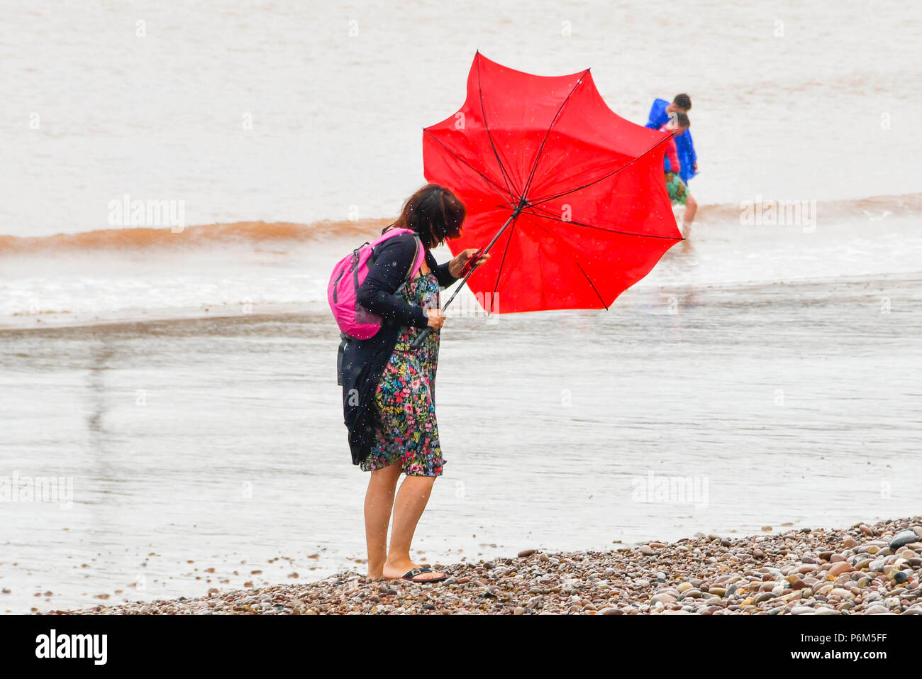 Sidmouth, Devon, UK.  1st July 2018. UK Weather.  A woman on the beach at the seaside resort of Sidmouth in Devon with umbrella which is caught by a gust of wind which turns it inside out as the town catches the edge of a passing heavy rain shower.  Picture Credit: Graham Hunt/Alamy Live News Stock Photo