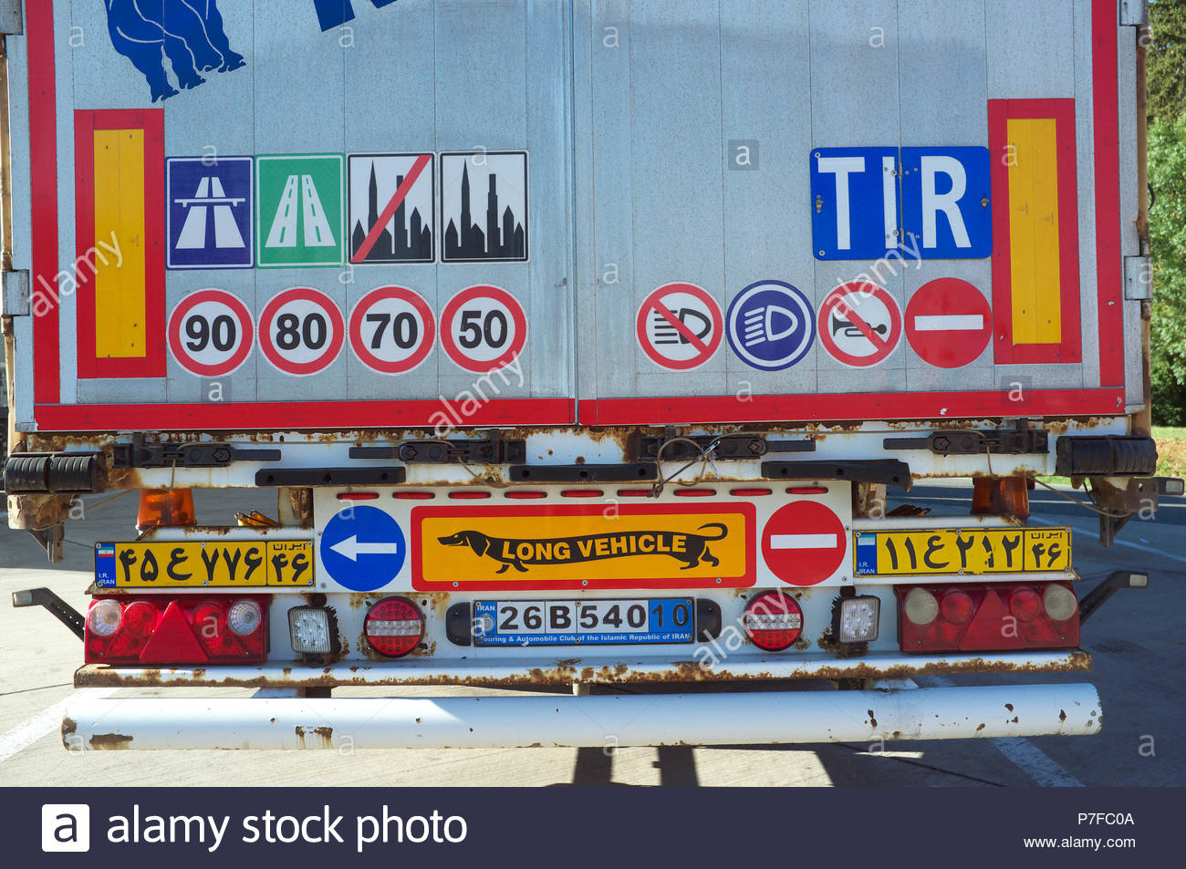 Rear of an Iranian registered truck, showing an assortment of highway code information signs, and a long vehicle (with dachshund dog) reflector plate. Stock Photo