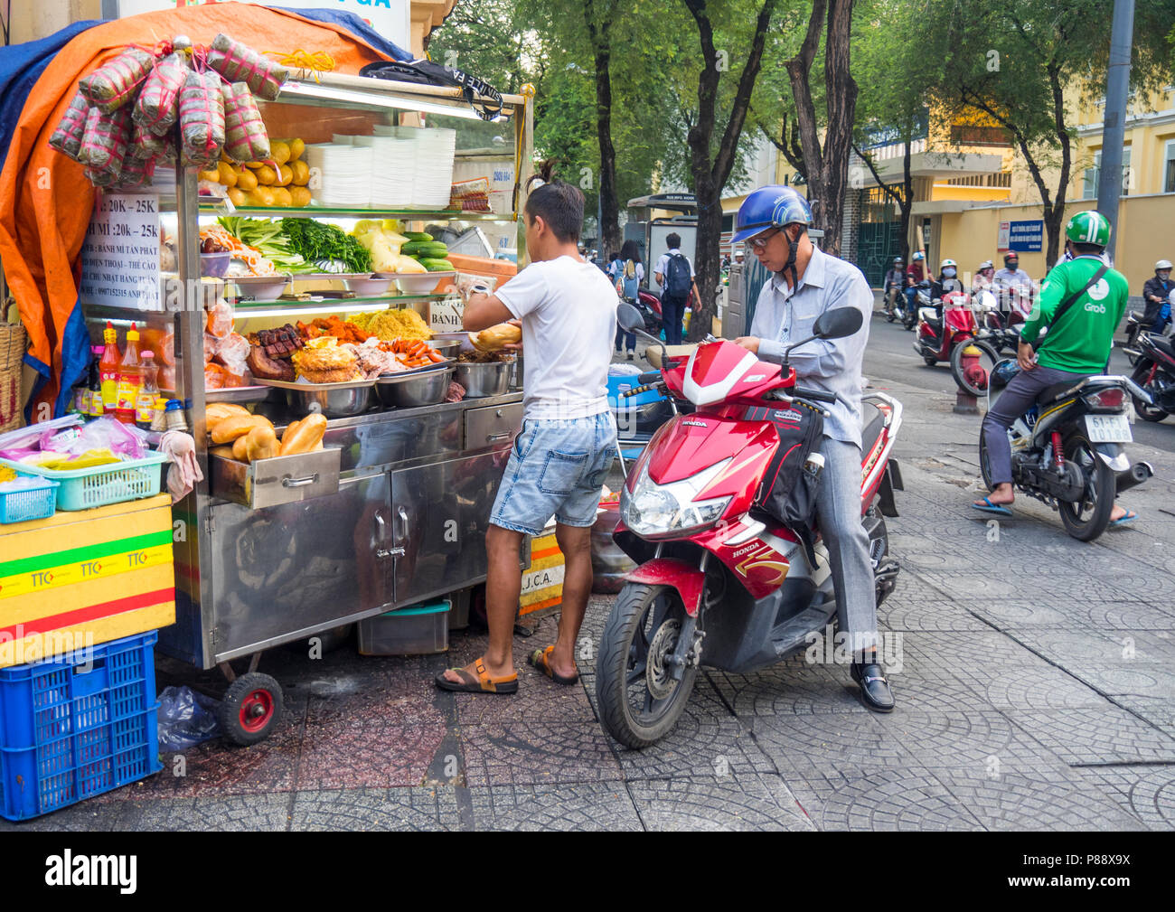 A Vietnamese man on a motorbike purchasing street food from a vendor selling food from a cart in Ho Chi Minh City Vietnam. Stock Photo