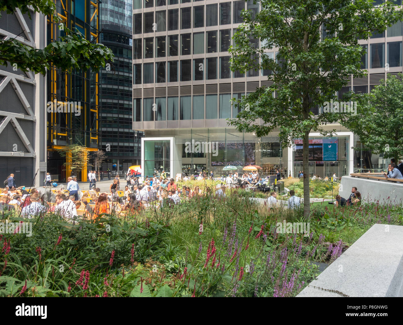 Tourists and local workers enjoying a sunny summer lunchtime in St Helen's Piazza, London. St Helen's Tower & Leadenhall Building. Flower beds, trees Stock Photo