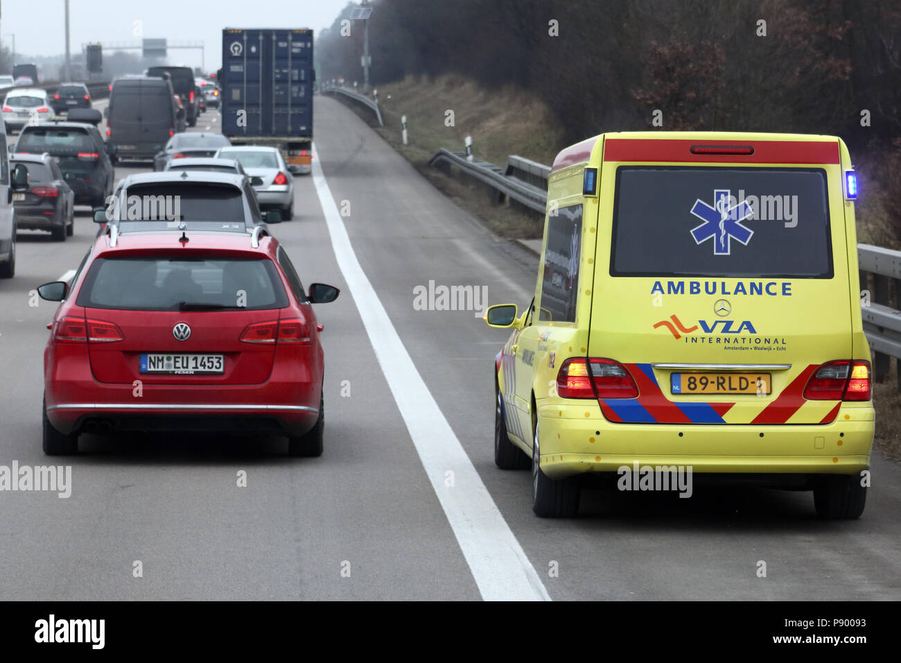 Nuernberg, Germany, Dutch ambulance drives on the traffic lane of the A9 past a traffic jam - Stock Image