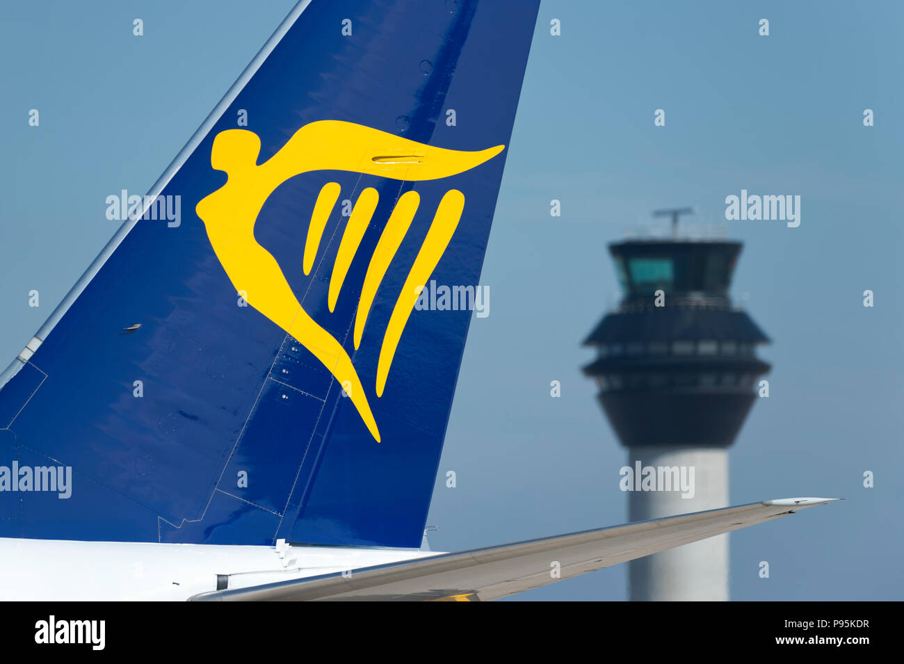 The tailfin of Ryanair Boeing 737-800 taxiing along the runway in front of the control tower at Manchester Airport. Stock Photo