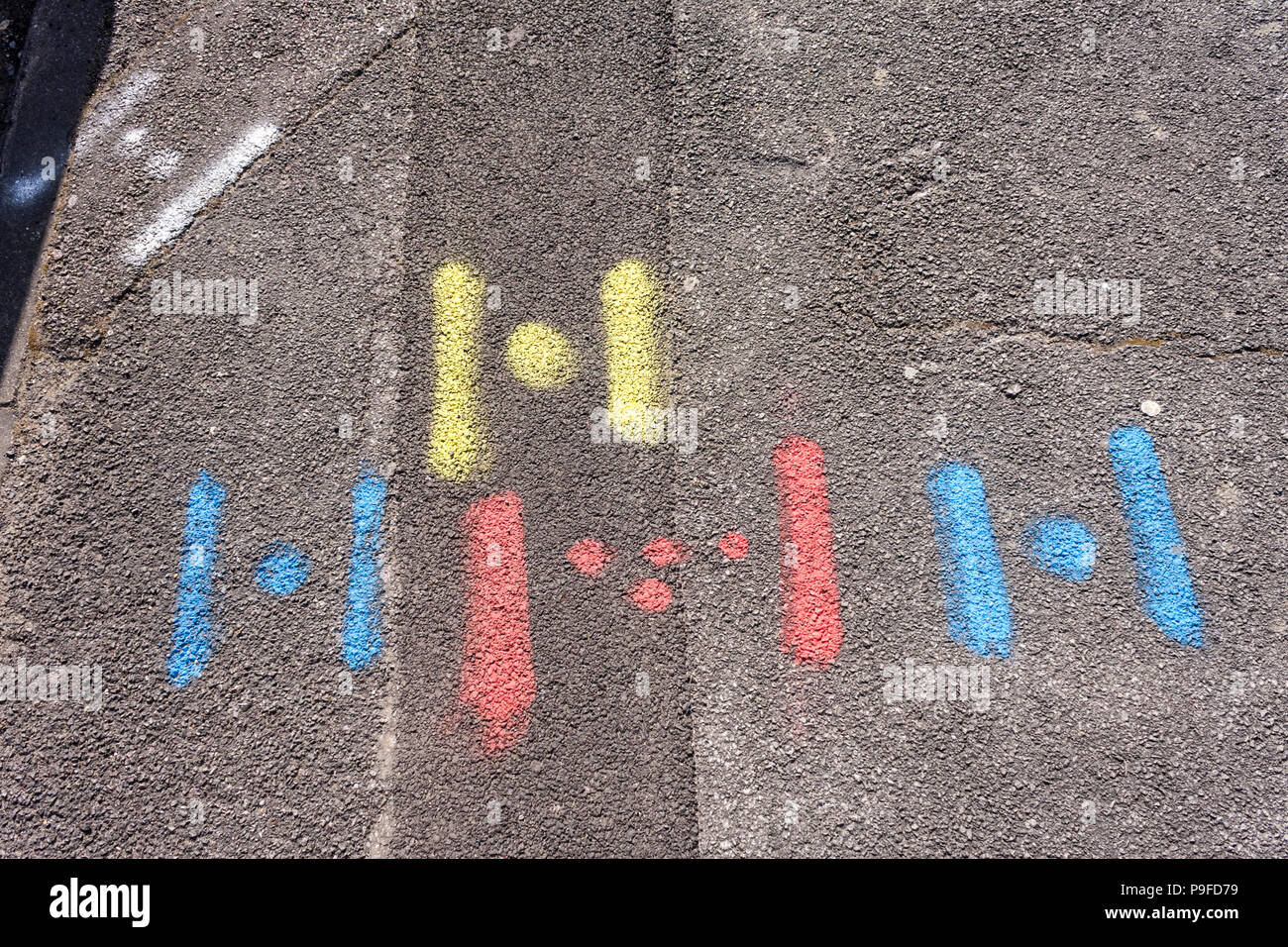 Spray painted markings left on road by contractors to indicate positioning of water, gas and electric utilities. Stock Photo