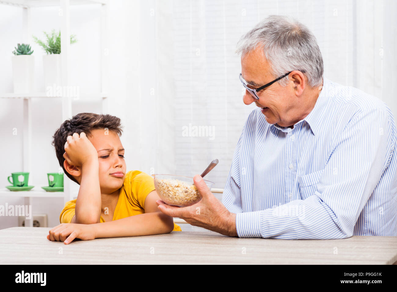Grandfather is giving oatmeal to his grandson but he refuses to eat it. Stock Photo