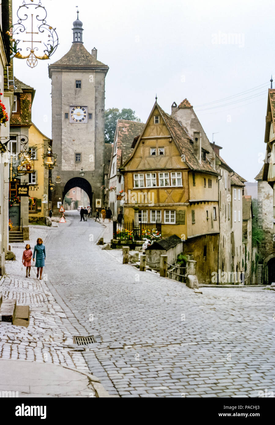 woman-and-girl-walking-down-old-cobbled-