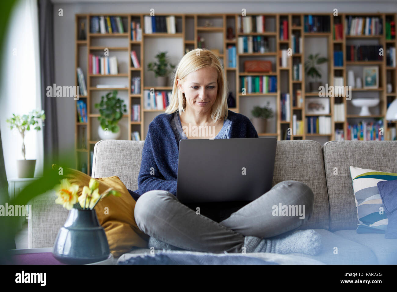 Woman at home sitting on couch using laptop Stock Photo