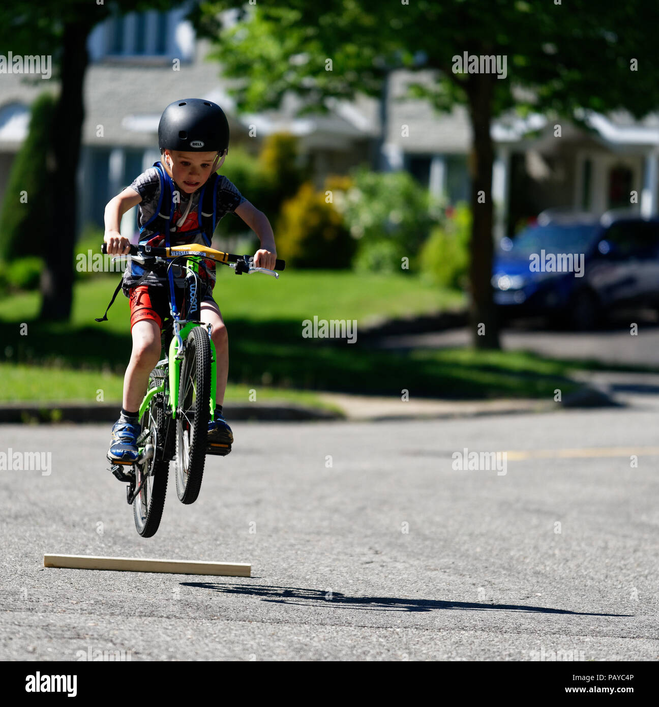 a-young-boy-6-yr-old-doing-jumps-in-the-street-on-his-bike-PAYC4P.jpg