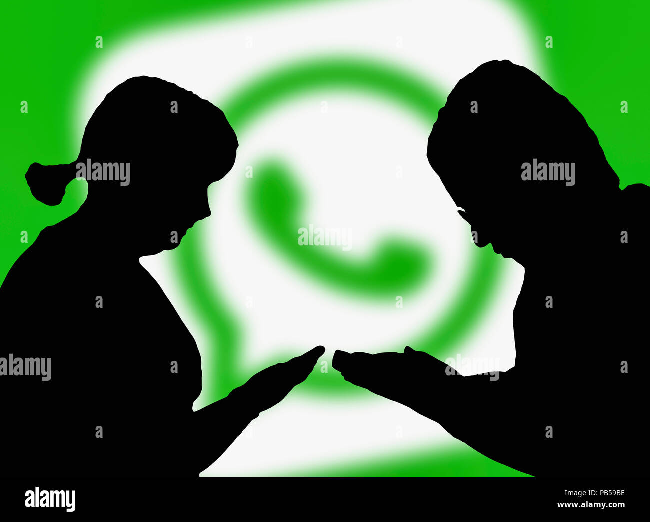 Silhouettes of a couple of people holding smartphones using the Whatsapp instant messaging app. Internet massaging online. Stock Photo