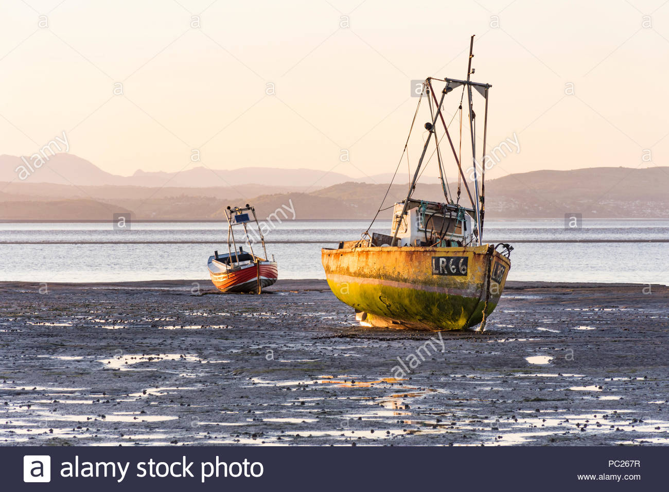 Boats moored in Morecambe Bay at low tide in the evening sunlight. Stock Photo