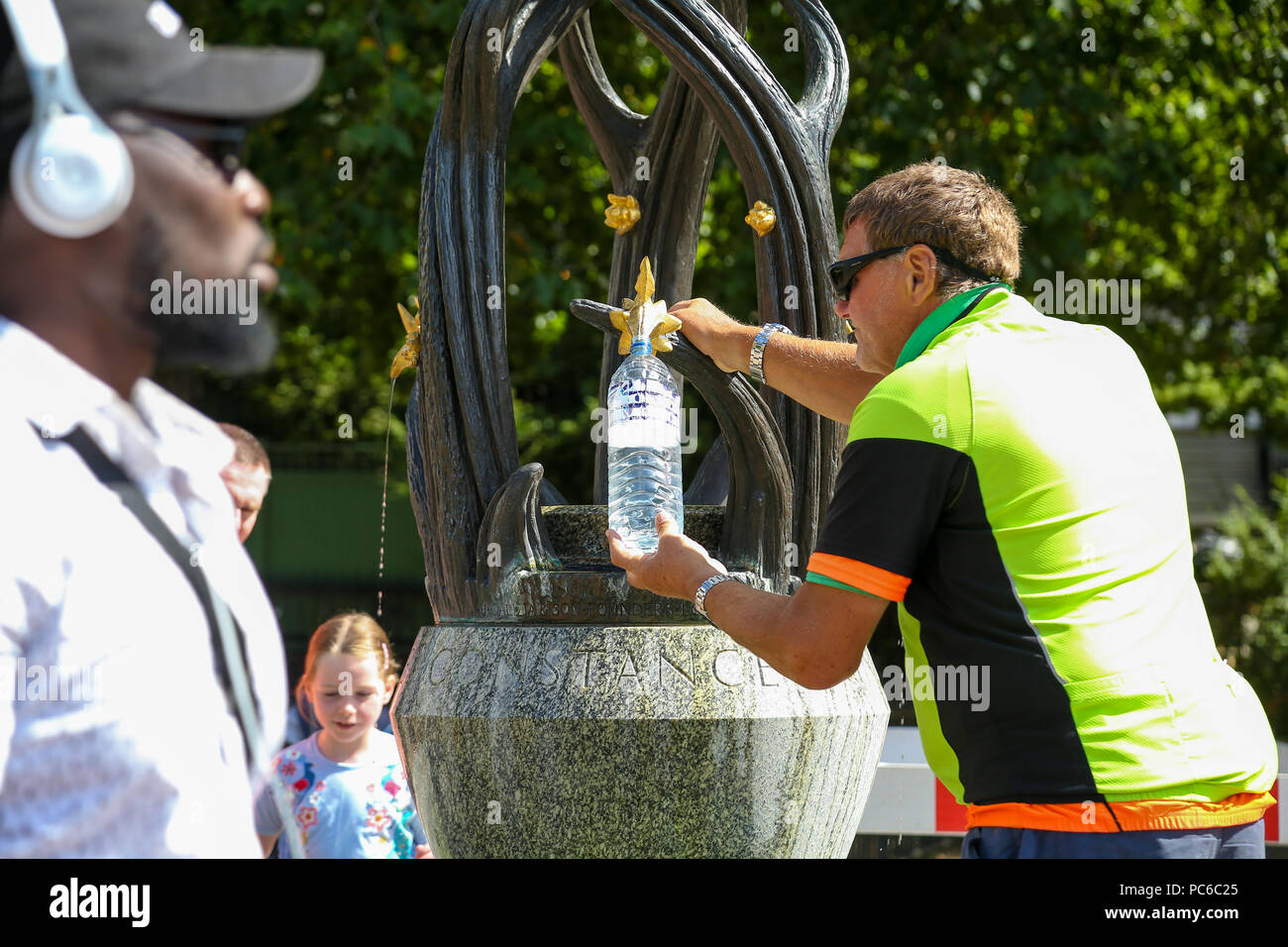 Green Park. London. UK 1 Aug 2018 - A man fill water bottles from the drinking fountain in Green Park on a sunny and warm day in the capital. According to The Met Office the heatwave is to return after a brief drop in temperature and rainfall in the UK as 32 degrees celsius is forecasted for the coming weekend.   Credit: Dinendra Haria/Alamy Live News Stock Photo