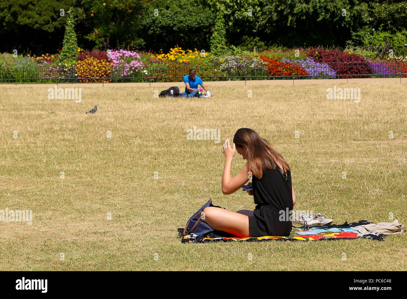 St James Park. London. UK 1 Aug 2018 - A woman relax on burnt grass in St James Park on a sunny and warm day in the capital. According to The Met Office the heatwave is to return after a brief drop in temperature and rainfall in the UK as 32 degrees celsius is forecasted for the coming weekend.   Credit: Dinendra Haria/Alamy Live News Stock Photo