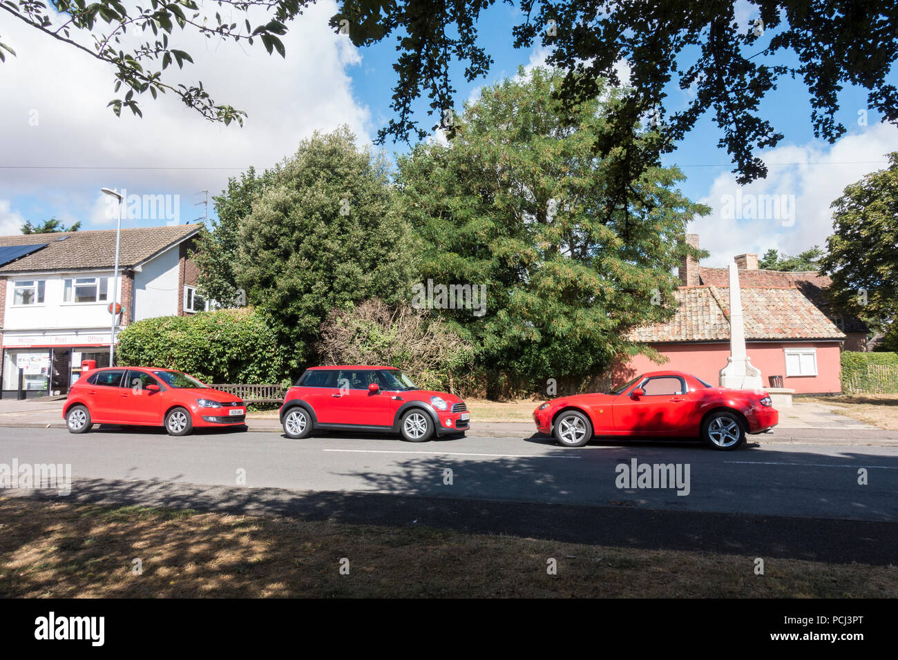 three-red-cars-parked-on-road-PCJ3PT.jpg