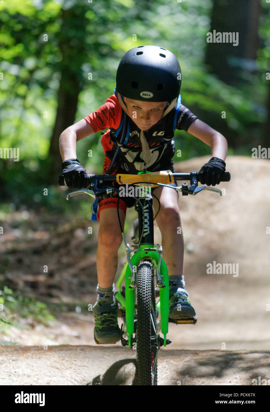a-young-boy-6-yr-old-riding-his-bike-looking-straight-at-the-camera-kingdom-trails-east-burke-vermont-usa-PCK67X.jpg