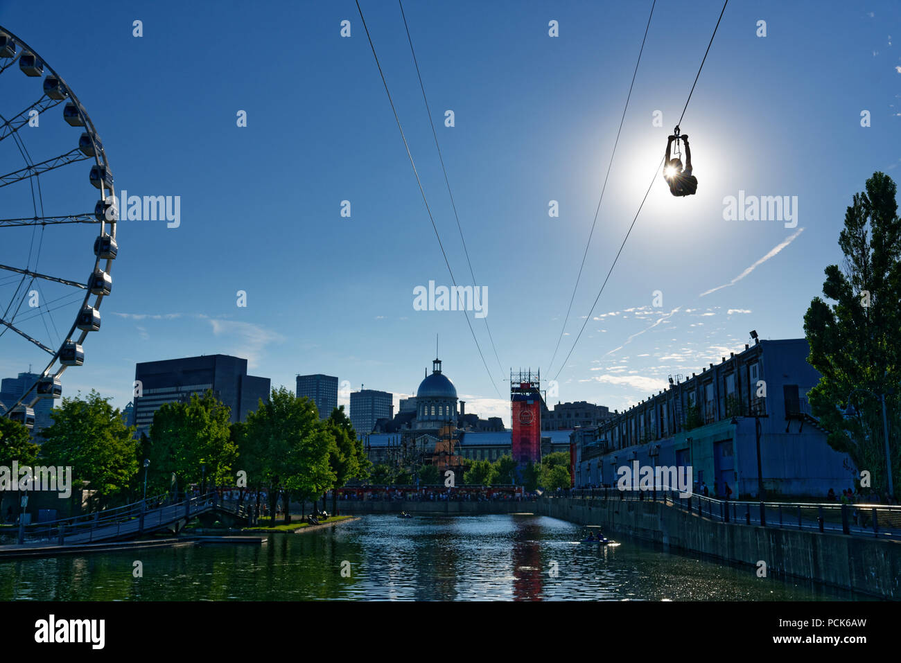 a-person-descending-the-zipline-in-montreal-old-port-with-la-grande-roue-de-montreal-behind-PCK6AW.jpg
