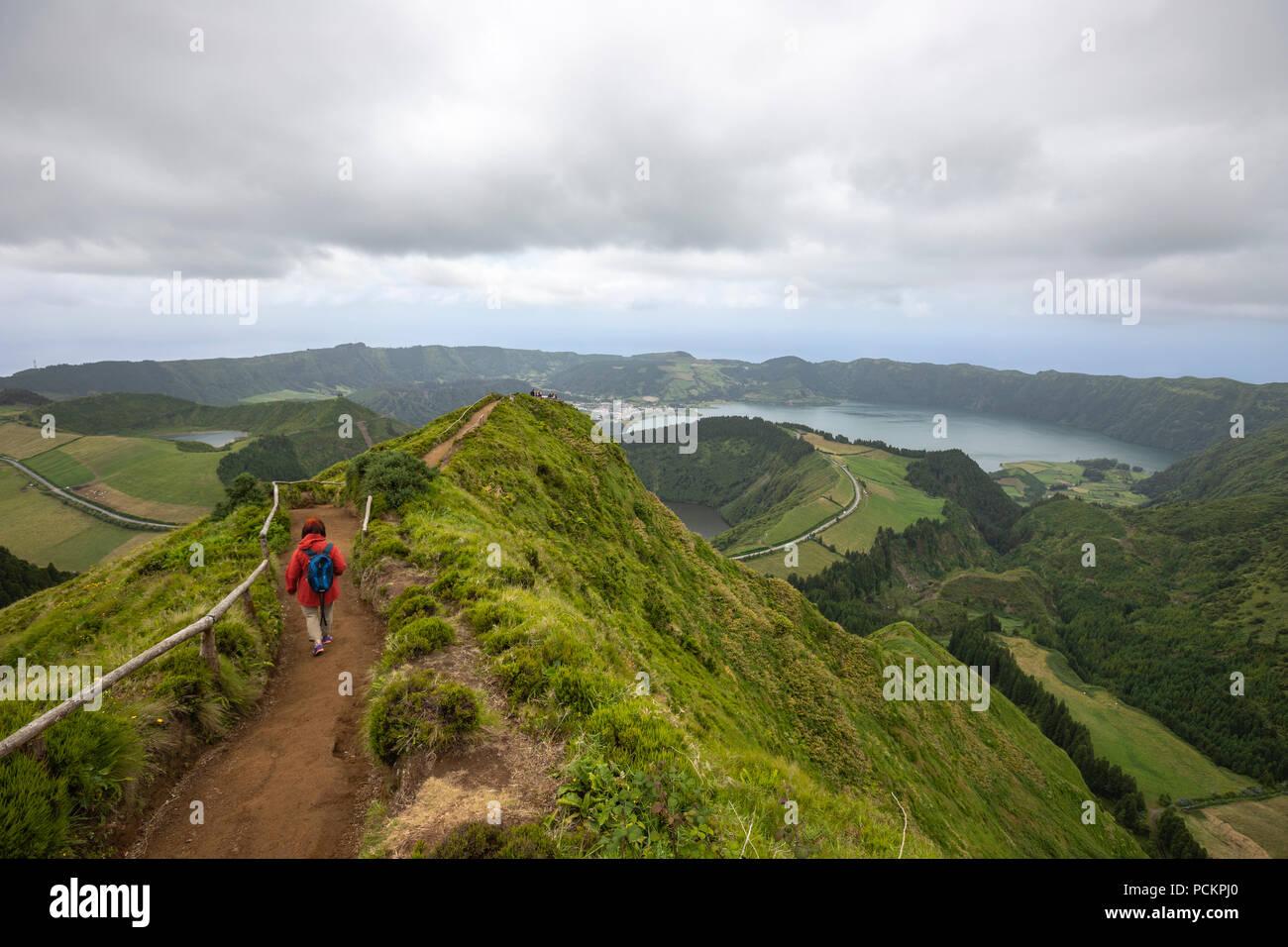 Tourists on a path leading to Lagoa do Canario Miradouro, viewpoint, and Santiago Lake and part of Sete Cidades Lake. Sao Miguel island, Azores. Stock Photo