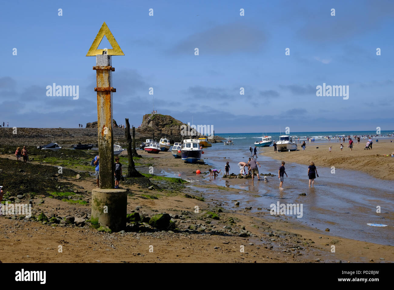 Bude, Cornwall, UK. Holidaymakers enjoy the beach at low tide at Breakwater Beach looking out into Sir Thomas's Pit and Summerleaze Beach Stock Photo