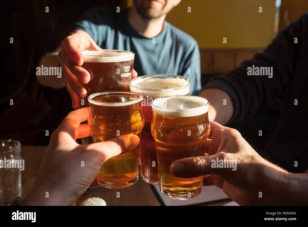 A party of four clink glasses (2 pints of cask ale and 2 half pints of cider) and say cheers at The Black Bull Inn in Frosterley, County Durham, UK. Stock Photo