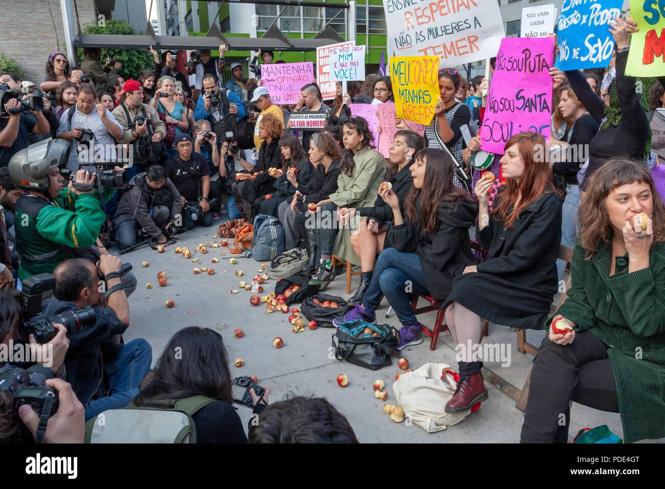 "'Marcha das Vadias' (Slut Walk) protest against sexual harassment. Women bite apples symbolizing the ""prohibited fruit"" at Avenida Paulista, Sao Paulo Stock Photo"