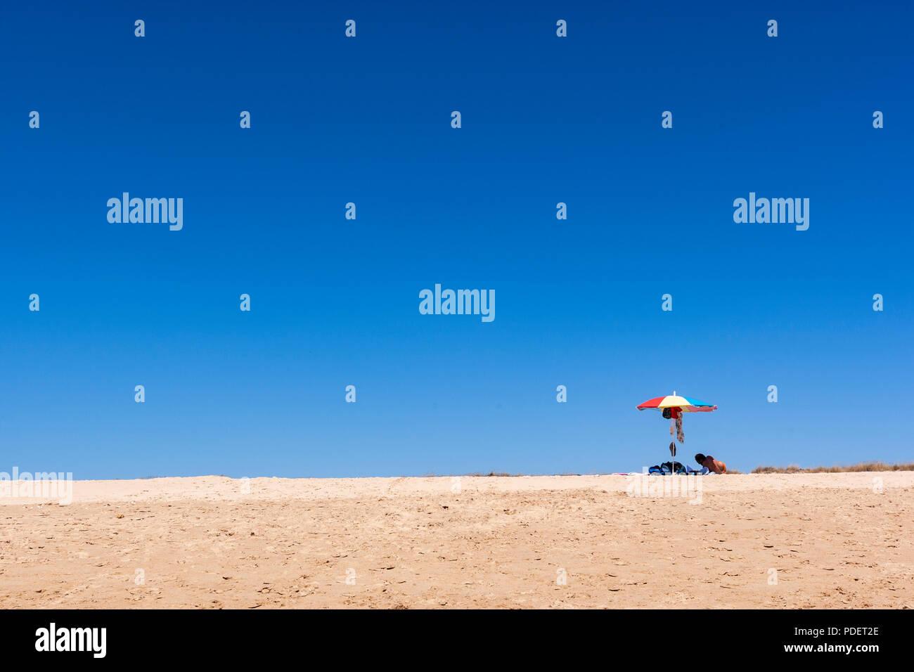 Isolated bather with parasol in the beach of Praia do Alvor, Alvor, Algarve, Portugal Stock Photo