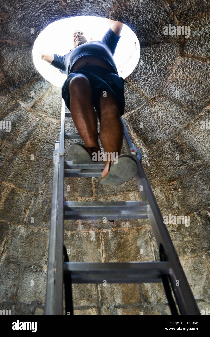 Lighthouse keeper at Forte do Cavalo lighthouse descends steep stairs Stock Photo