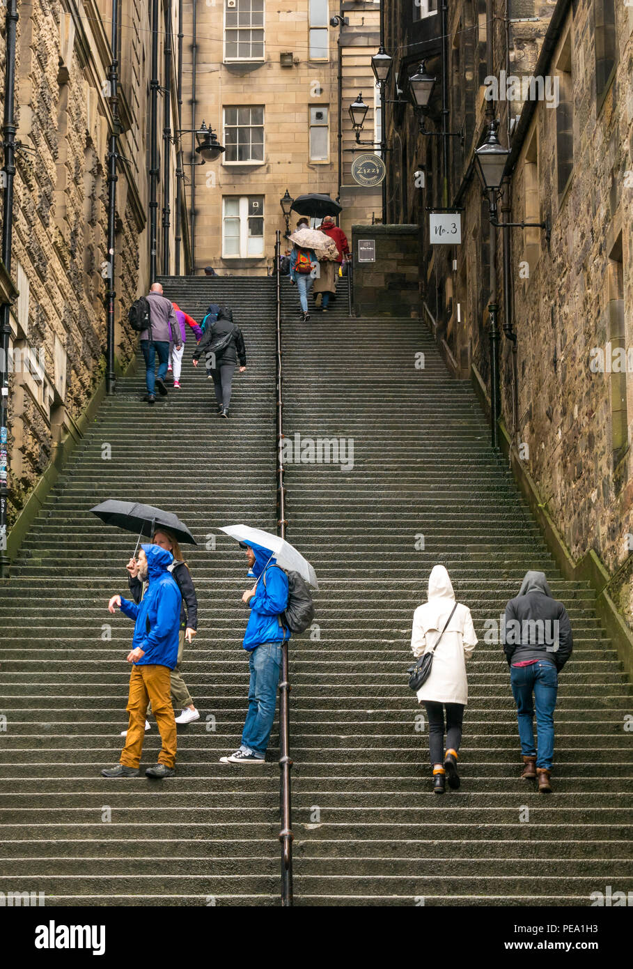 tourists-with-umbrellas-in-rain-walking-