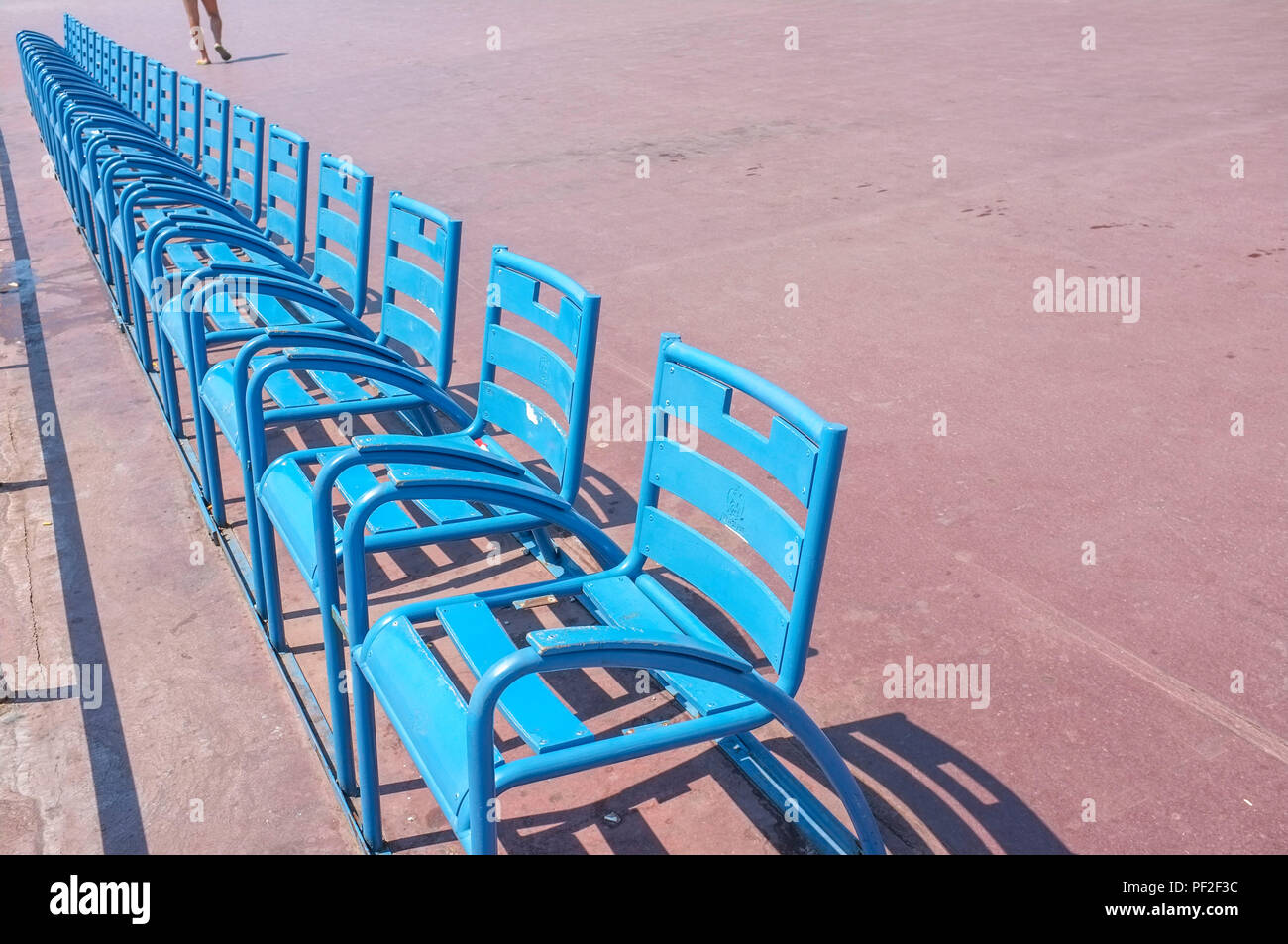 a-man-walk-by-the-blue-chairs-on-the-pro