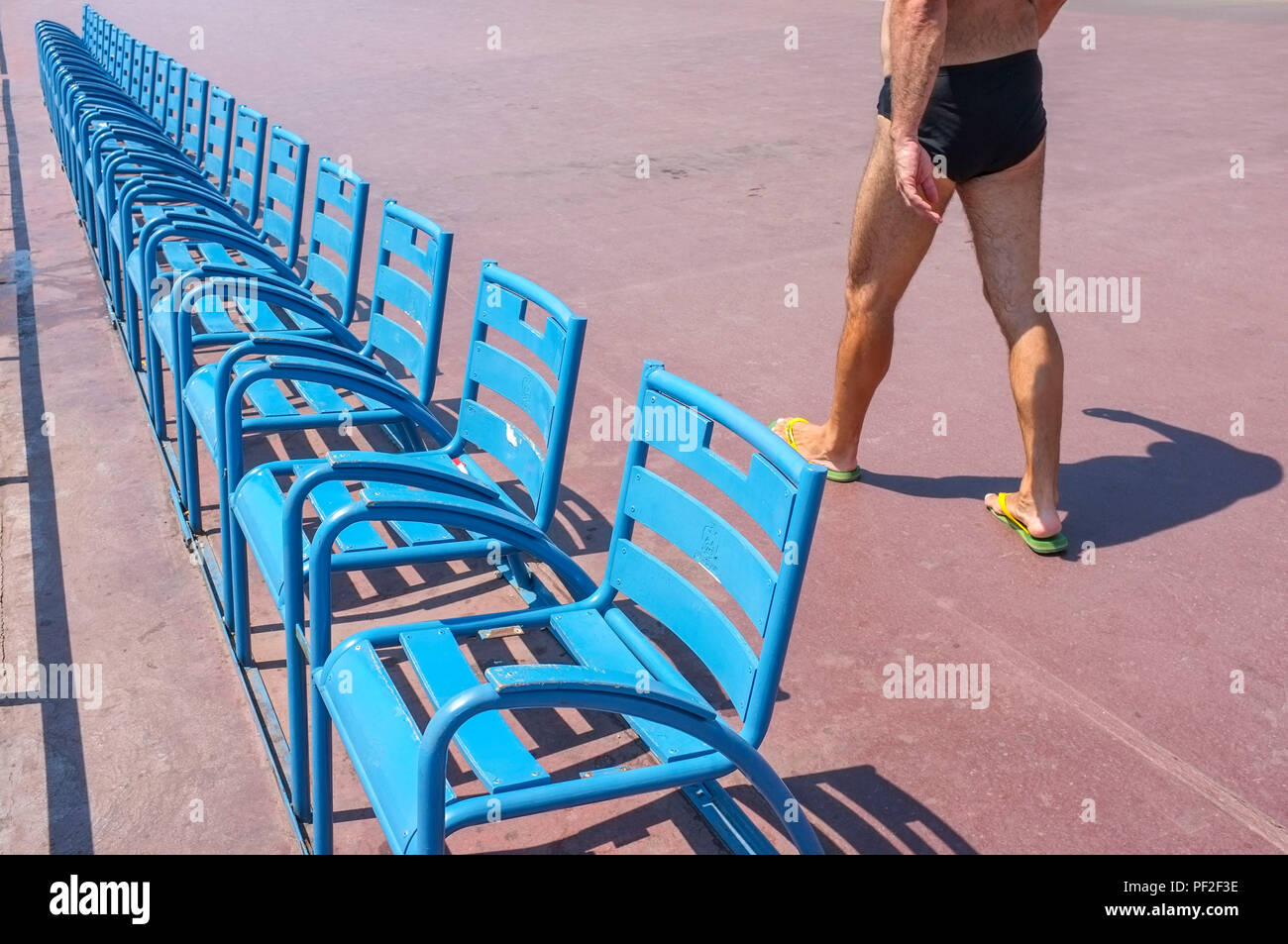 a-man-walk-by-the-blue-chairs-on-the-promenade-des-anglais-in-nice-france-PF2F3E.jpg