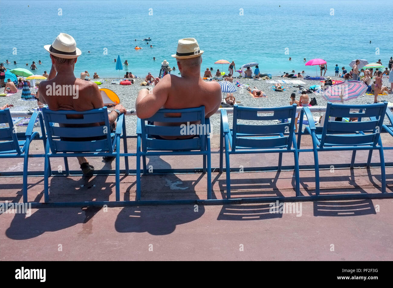 two-men-sit-on-the-blue-chairs-on-the-pr