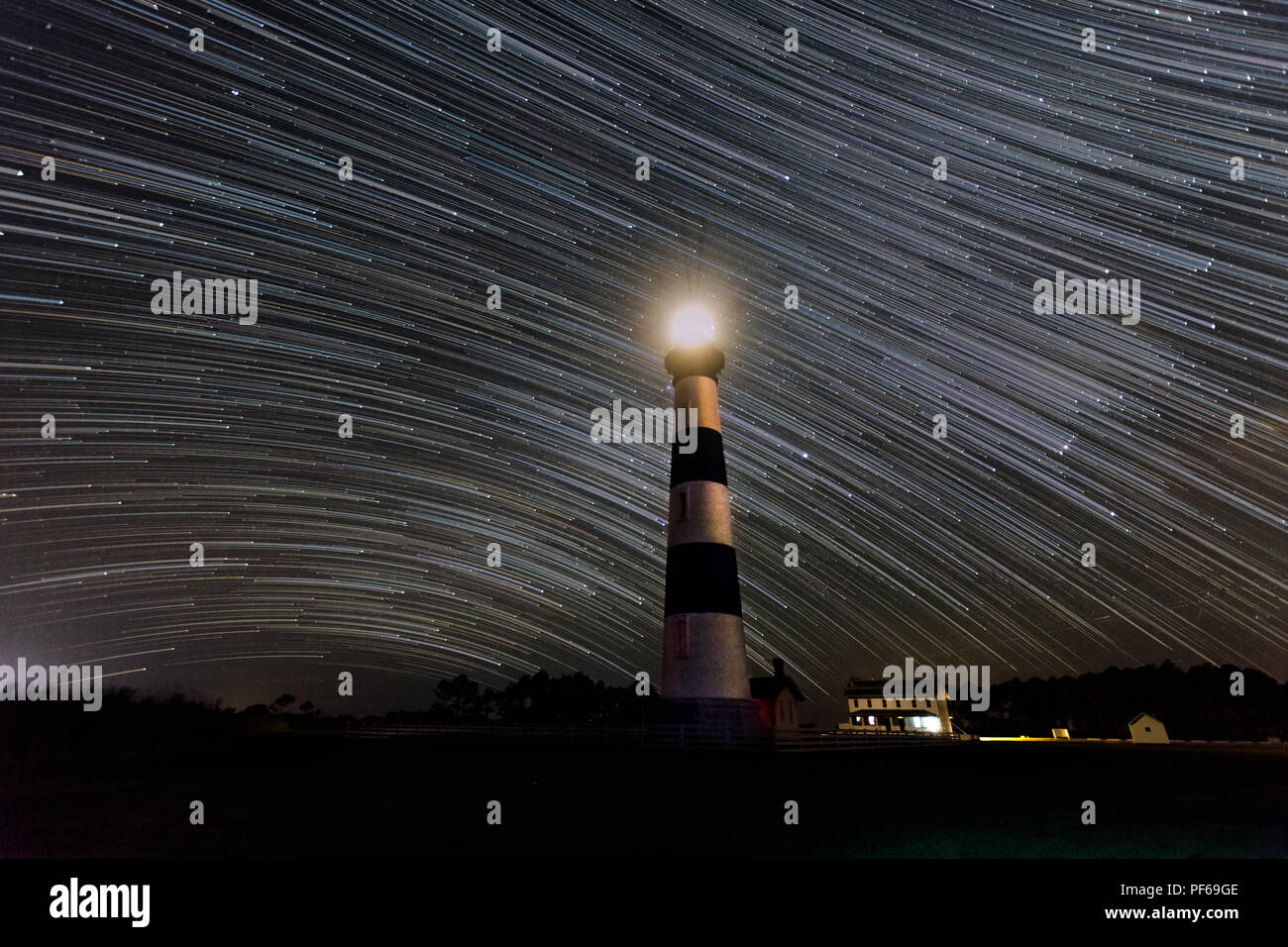 Stars streak by the Bodie Island Lighthouse in Cape Hatteras National Seashore in the Outer Banks of North Carolina in this long exposure night sky Stock Photo