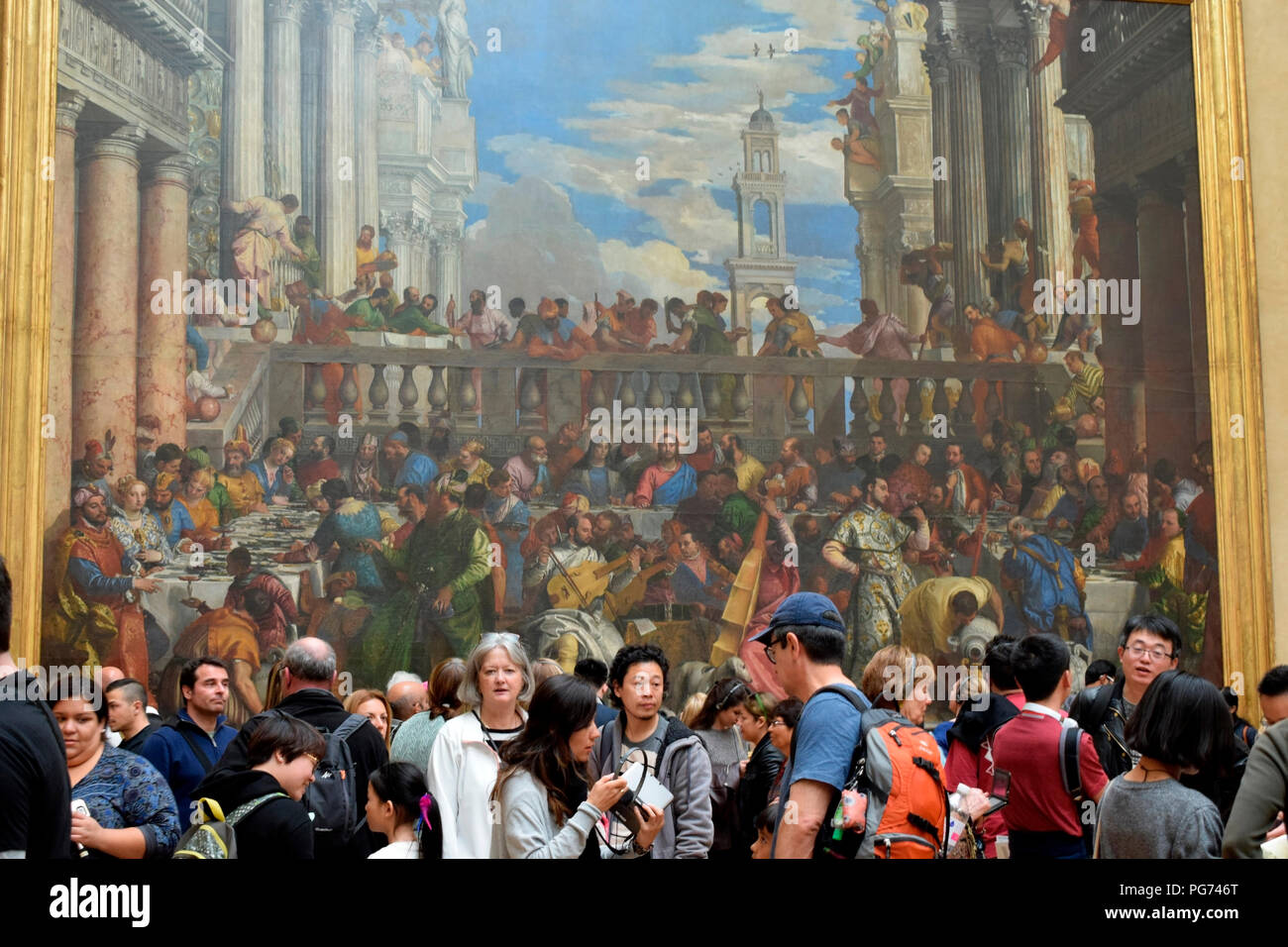 Visitors in front of The Wedding Feast at Cana by Veronese, the largest painting in the Louvre gallery, Paris,France Stock Photo