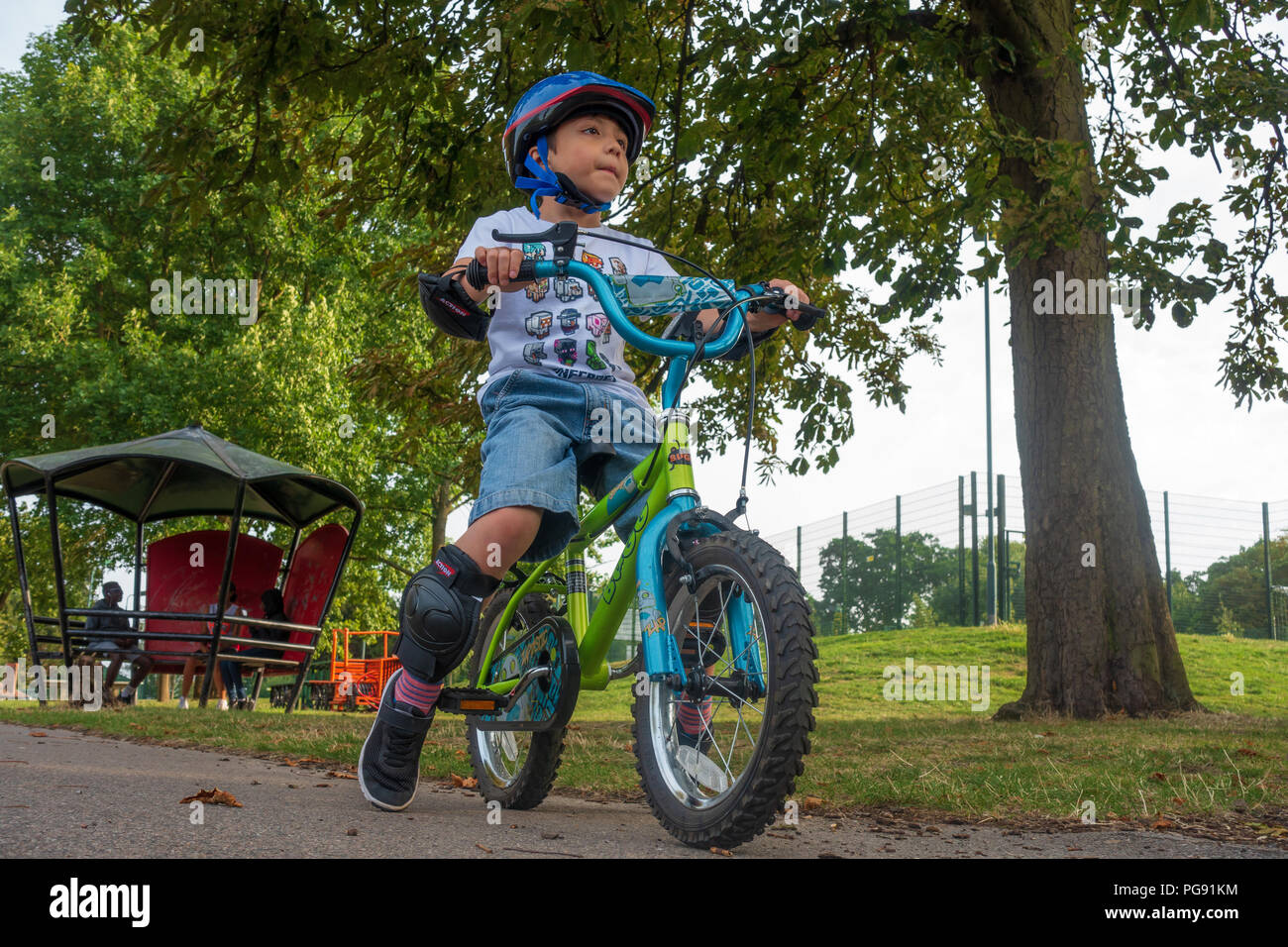 a-young-boy-rides-his-bicycle-in-prospect-park-in-reading-uk-he-is-wearing-a-bicycle-helmet-and-protective-knee-and-elbow-pads-PG91KM.jpg