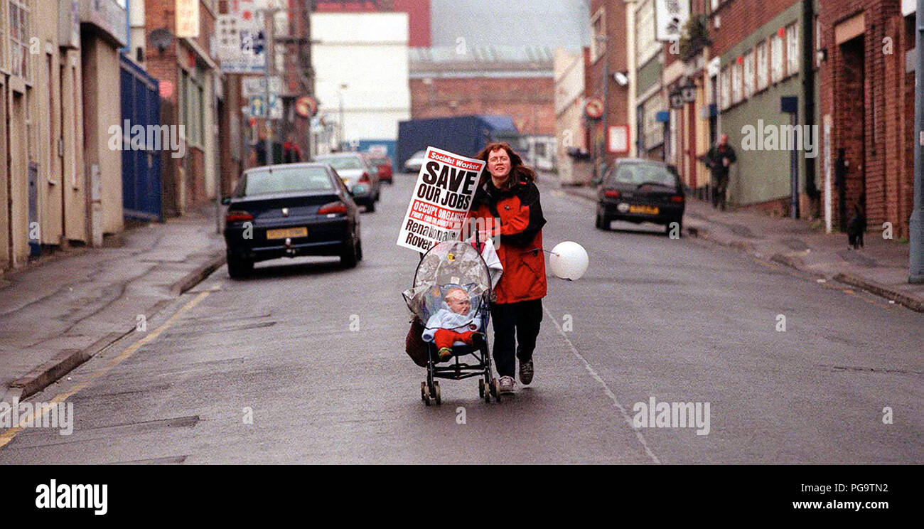 A woman with a baby in pushchair hurries to join a Save Our Jobs rally for the Rover plant at Longbridge, Birmingham, April 2000 Stock Photo