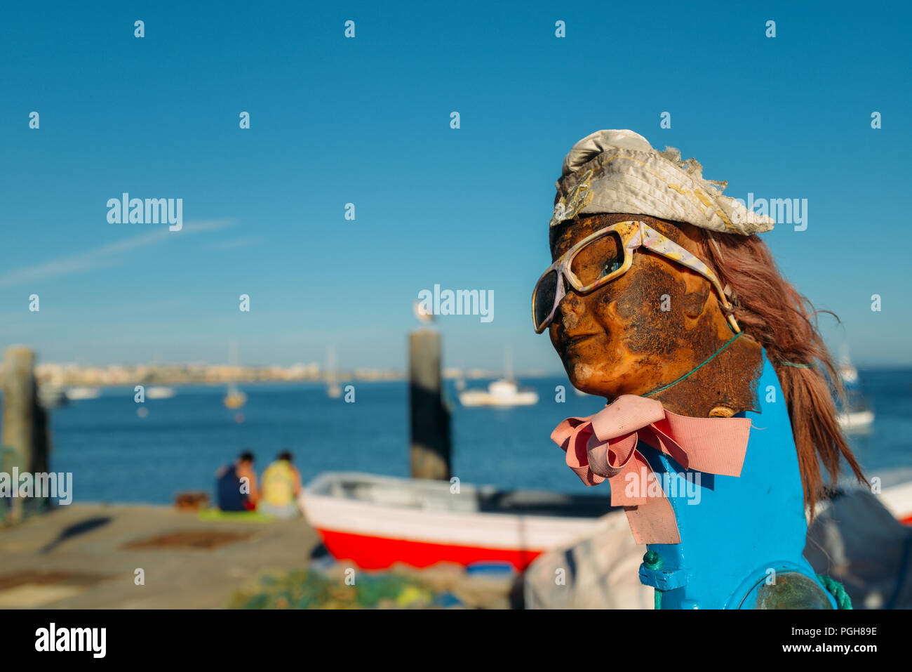 face-of-dirty-doll-with-sunglasses-and-ponytail-on-mast-of-a-wooden-boat-PGH89E.jpg