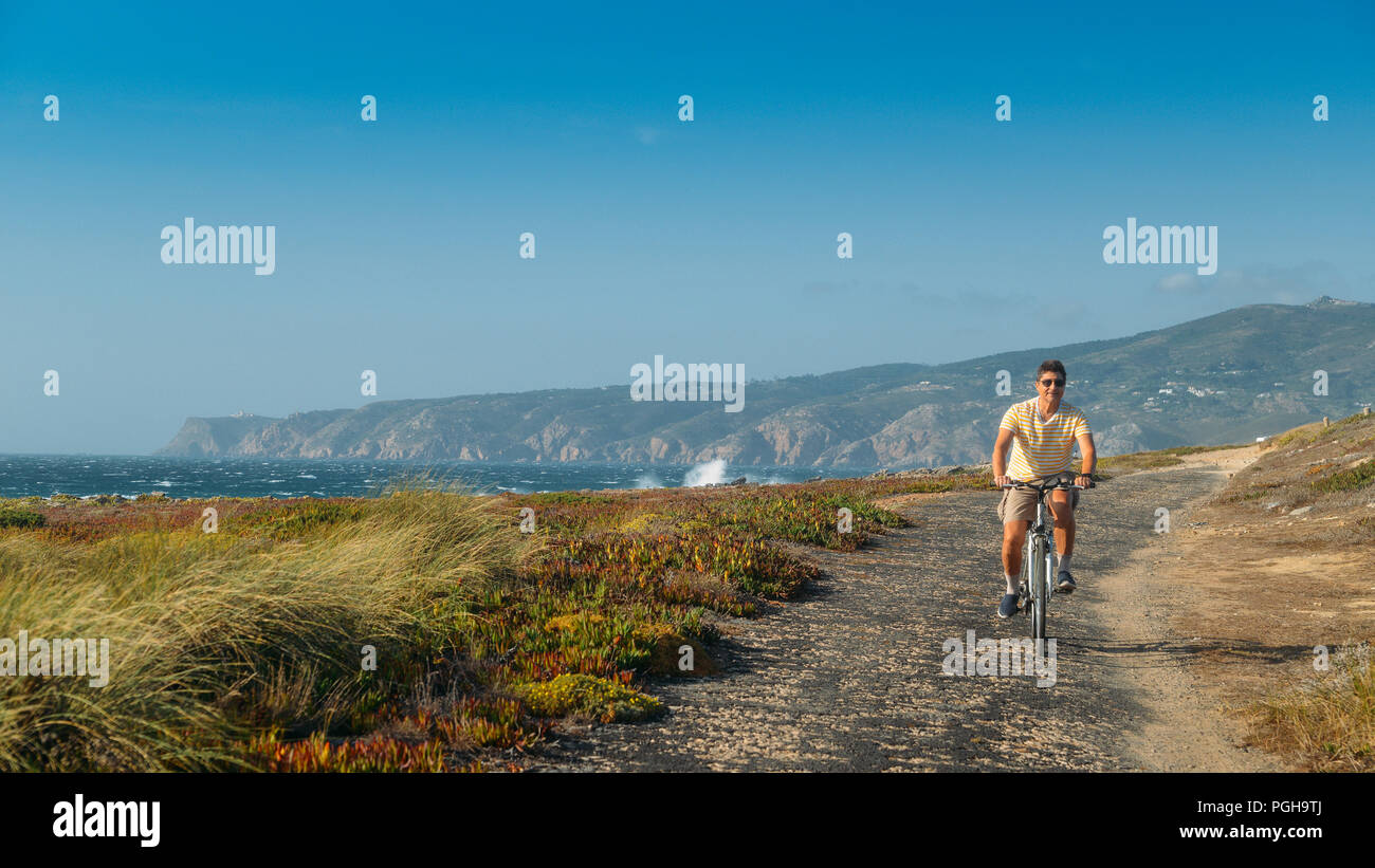 mature-man-55-60-cycles-along-a-bumpy-asphalt-path-overlooking-praia-do-guincho-and-roca-do-cabo-near-cascais-portugal-during-a-windy-summer-day-PGH9TJ.jpg