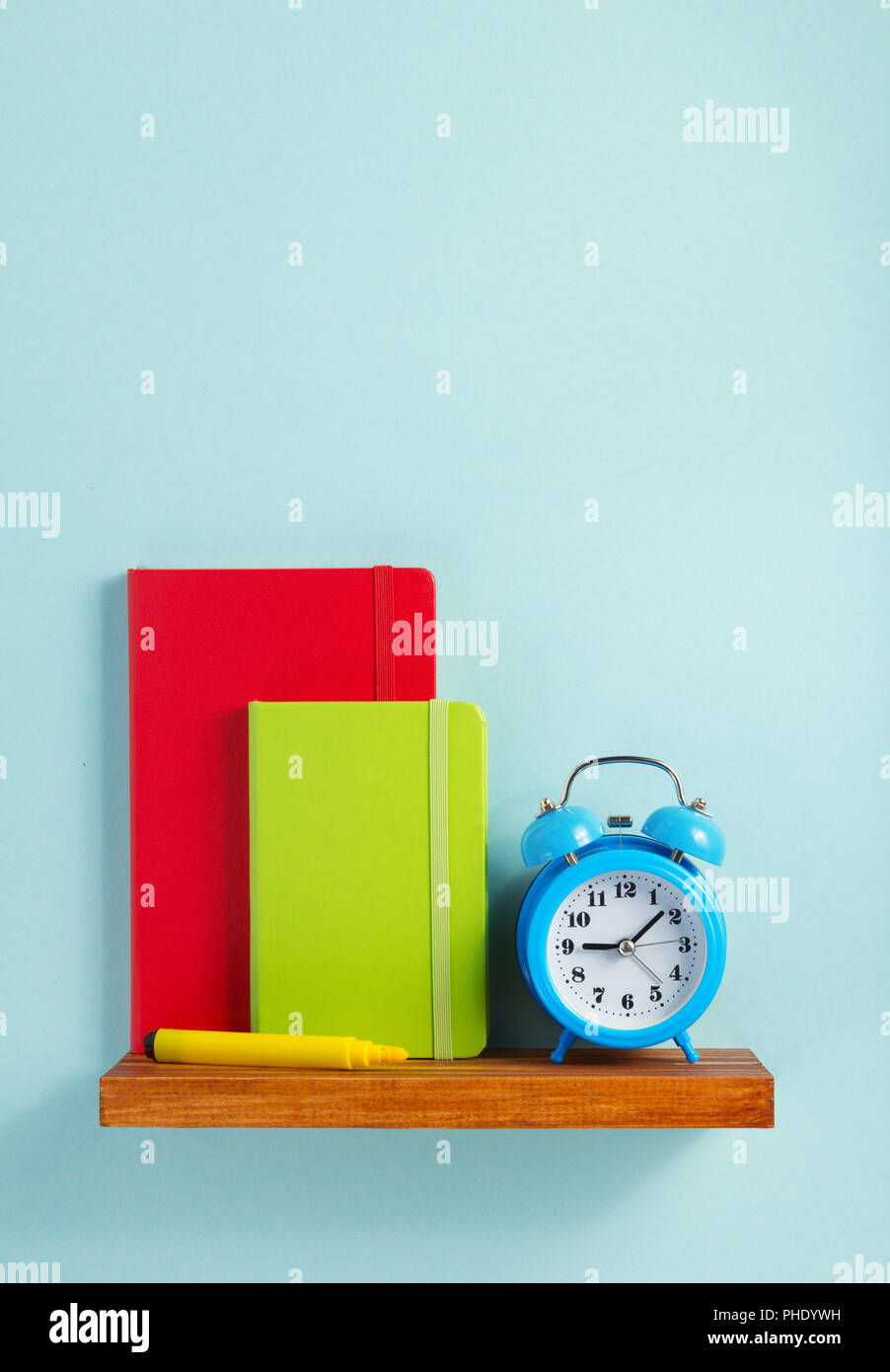 notepad and book on shelf at wall background surface Stock Photo
