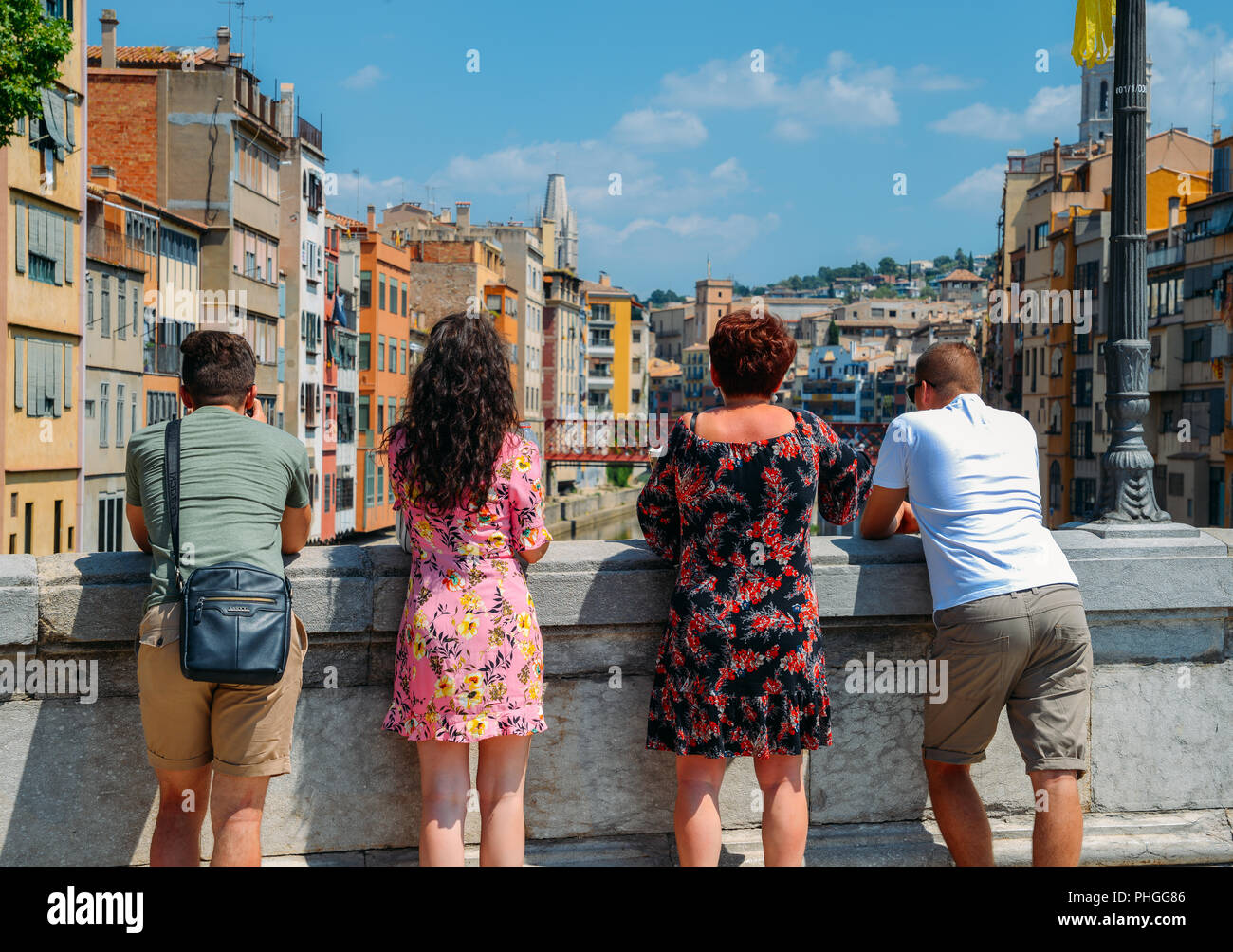 girona-spain-july-9-2018-family-of-tourists-overlook-colorful-red-and-yellow-houses-and-bridge-river-onyar-girona-is-a-famous-tourist-spot-PHGG86.jpg