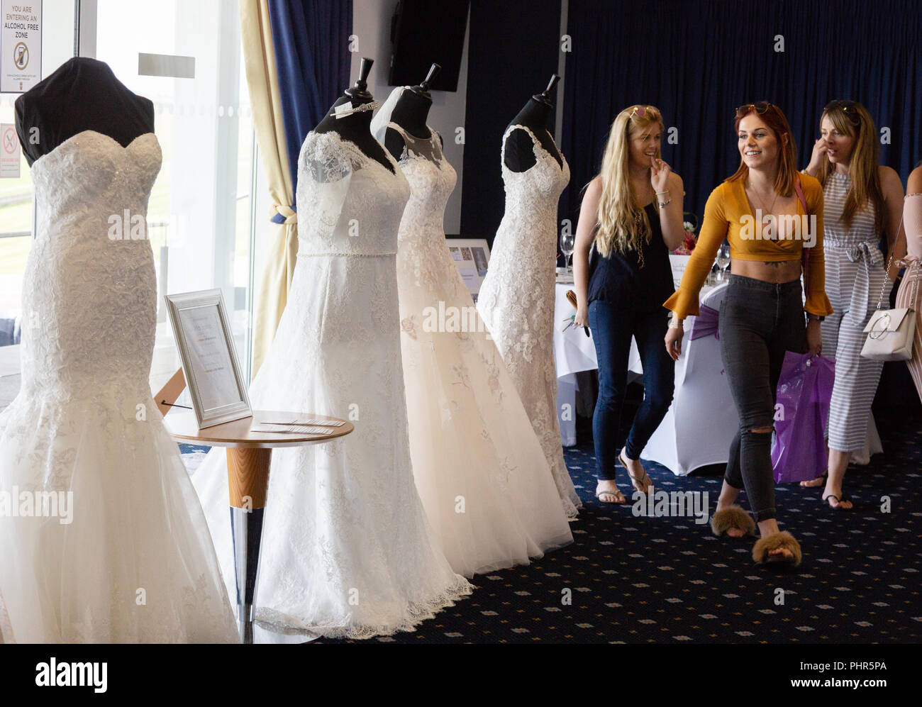 women-shopping-for-wedding-dresses-at-a-wedding-fair-newmarket-suffolk-uk-PHR5PA.jpg