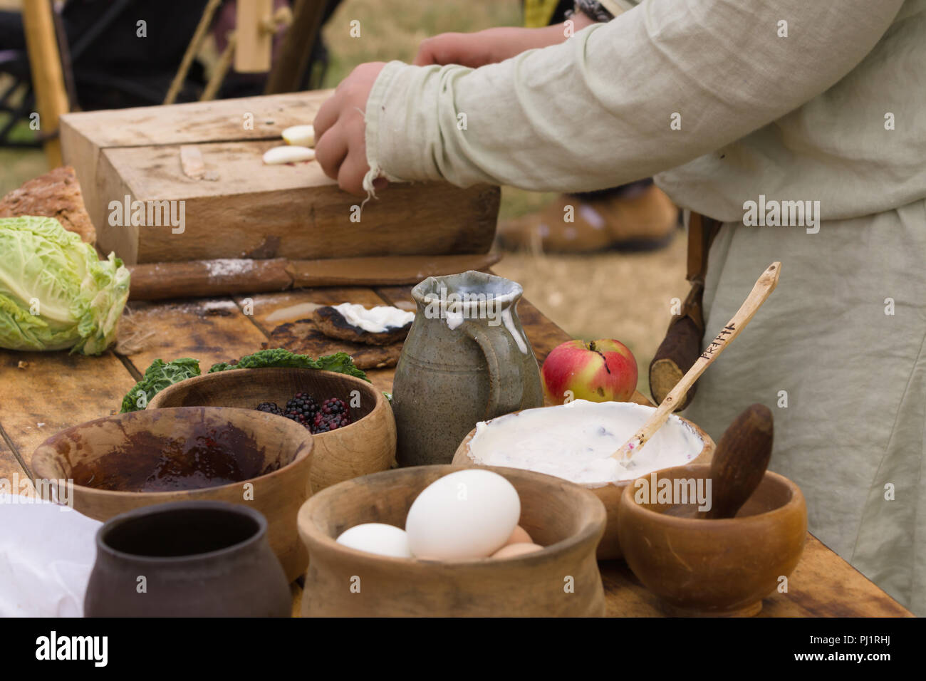 Medieval food preparation including bread, butter, cheese, fruit in wooden bowls or trenchers Stock Photo