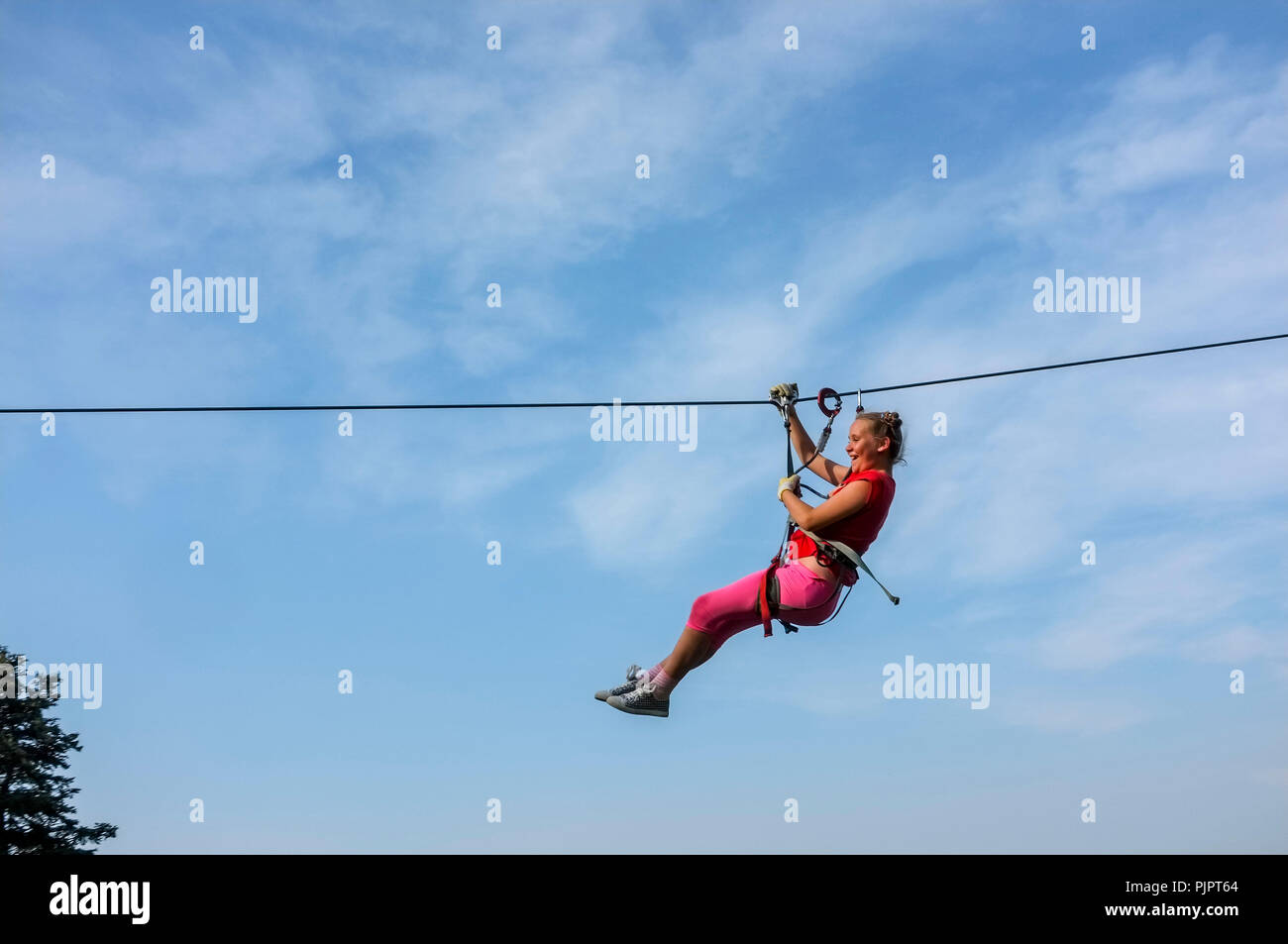 pre-teen-girl-on-a-zip-line-against-the-sky-PJPT64.jpg