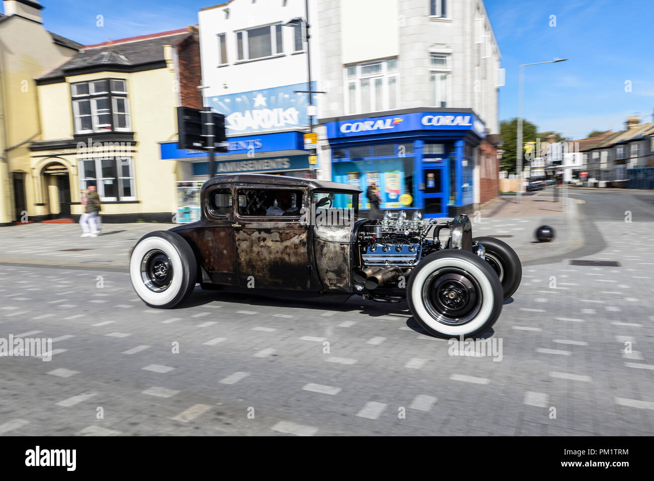 custom-car-hot-rod-coupe-driving-along-southend-on-sea-seafront-white-wall-tires-tyres-rusty-bare-metal-with-clear-coat-finish-PM1TRM.jpg