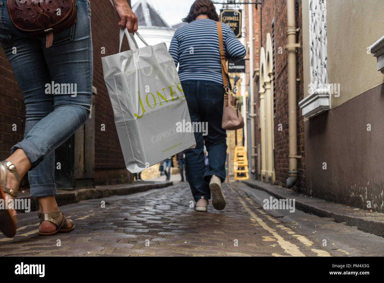 low-angle-ground-level-view-of-female-shoppers-with-carrier-bags-walking-down-a-narrow-street-in-windsor-uk-PM4X3G.jpg