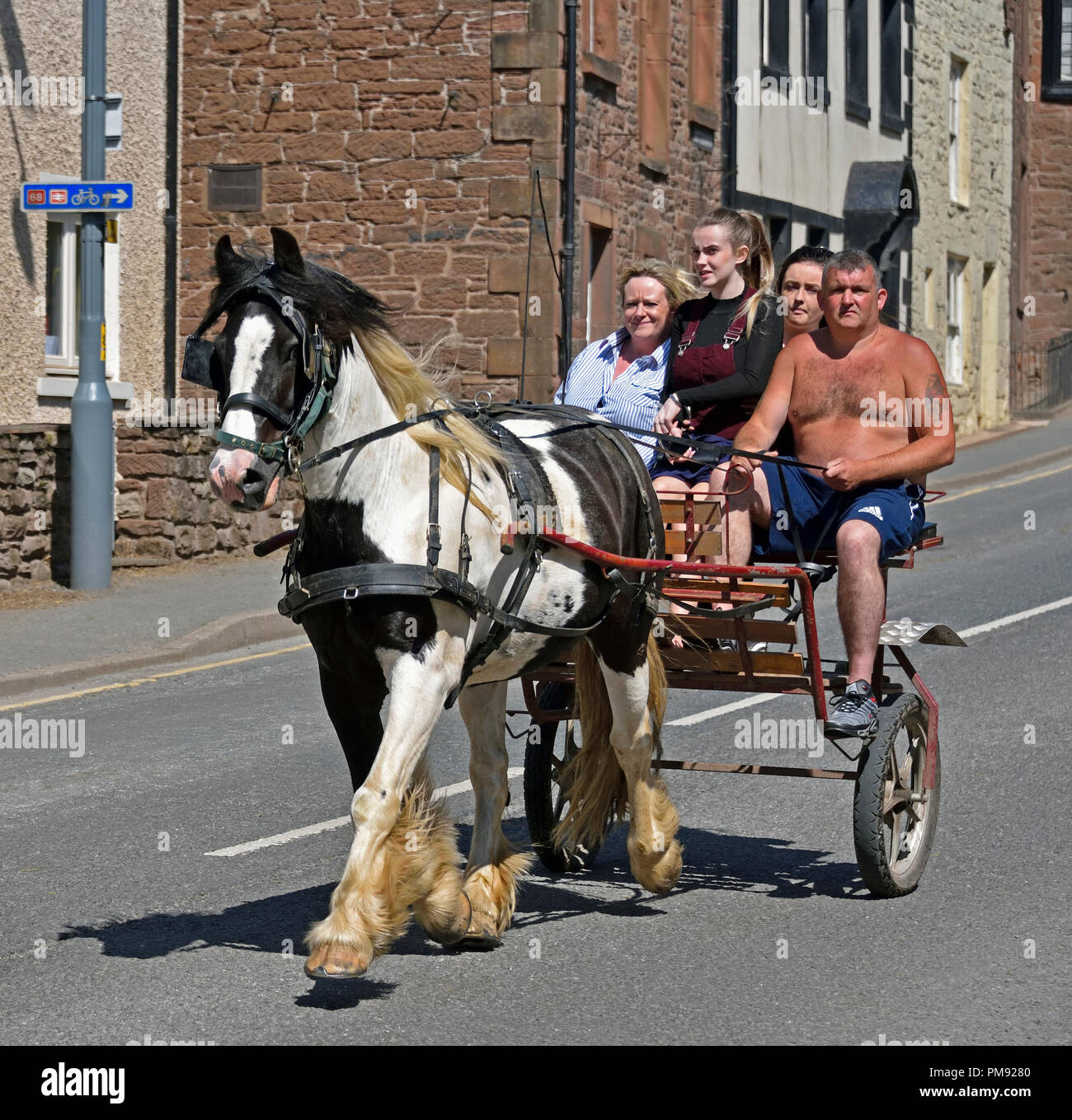 gypsy-traveller-family-riding-on-trotting-cart-appleby-horse-fair-2018-the-sands-appleby-in-westmorland-cumbria-england-united-kingdom-europe-PM9280.jpg