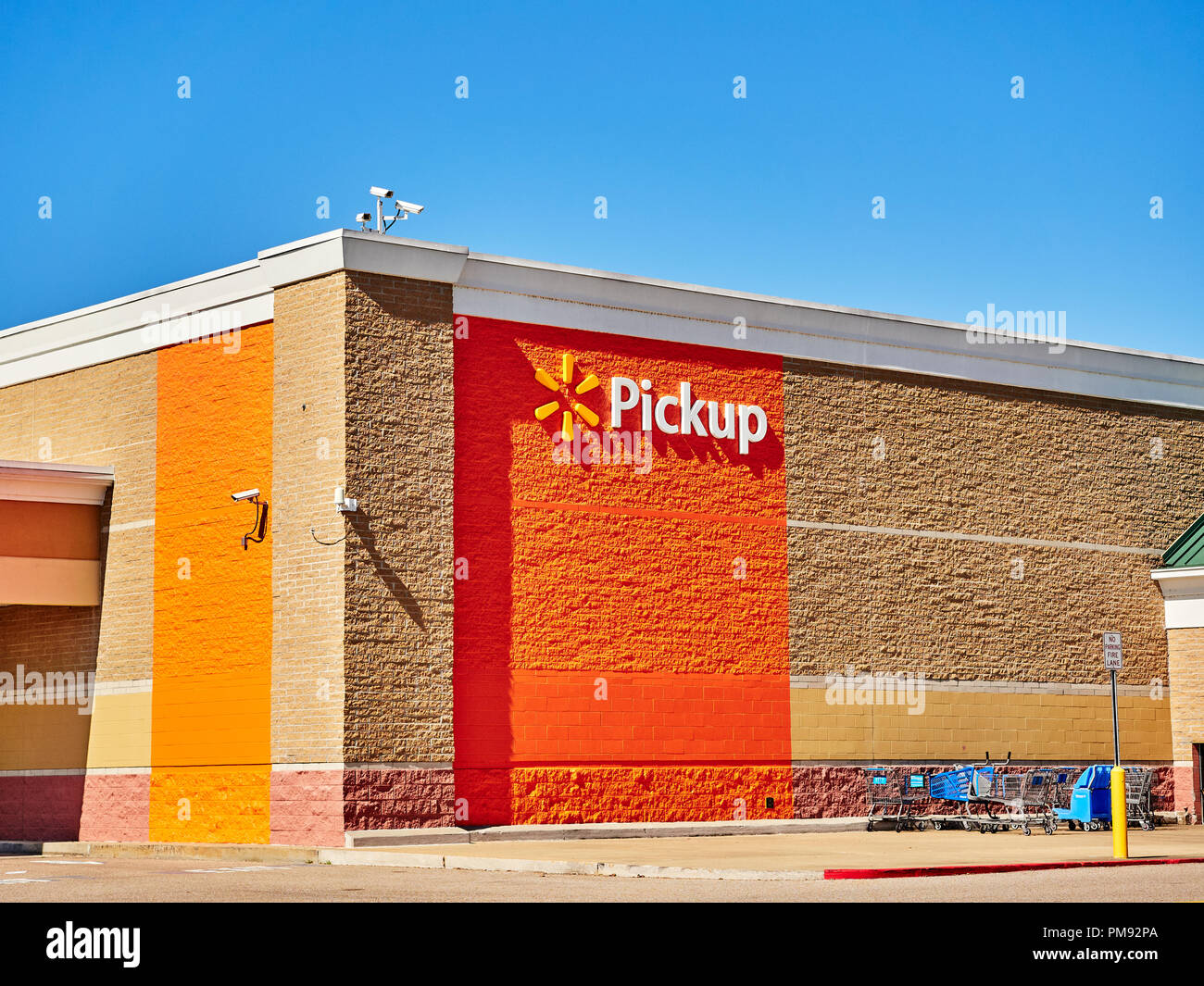 Walmart pickup sign and corporate logo on exterior wall of a super Walmart store in Montgomery Alabama, USA. Stock Photo