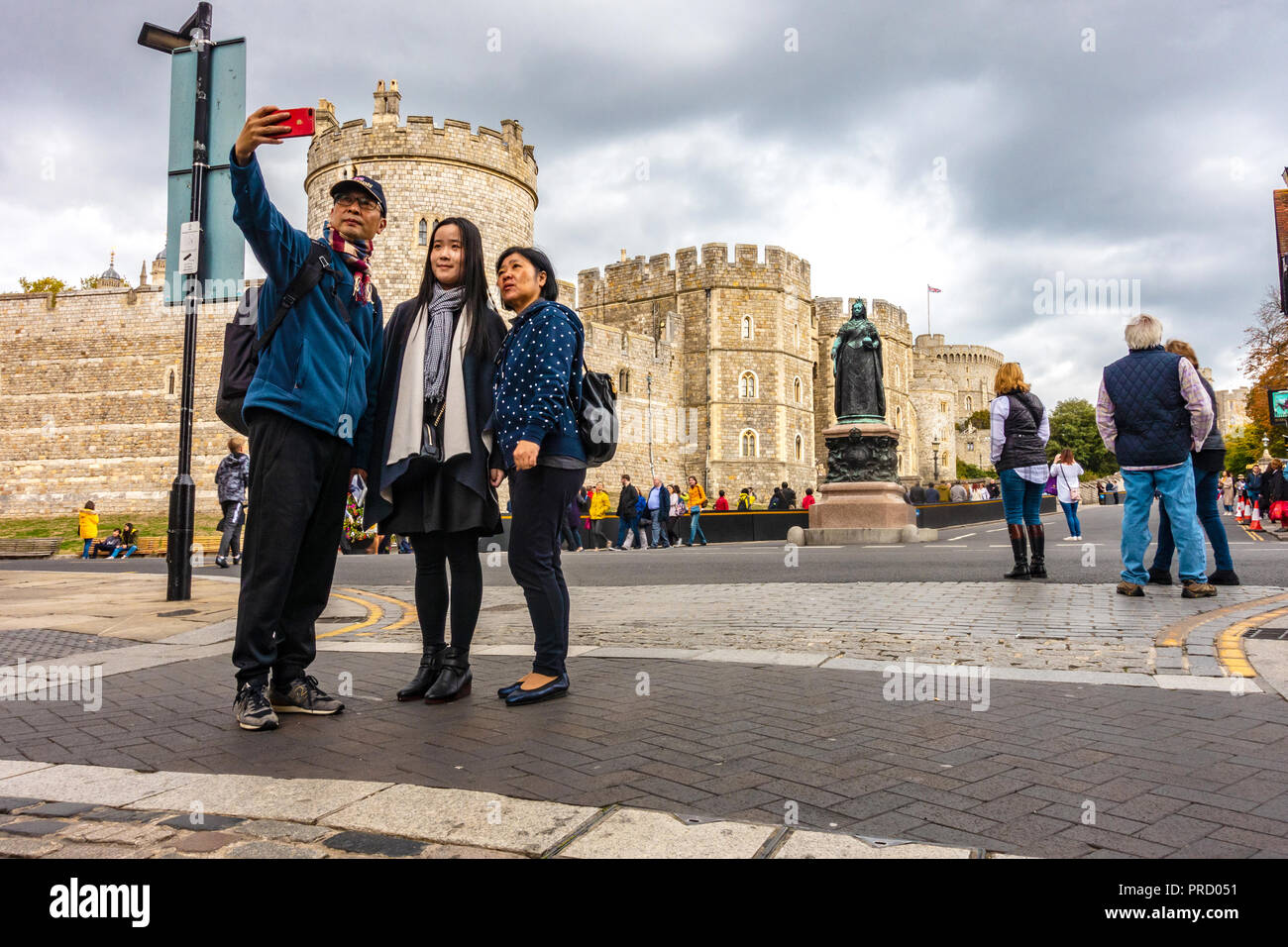 a-tourist-asian-family-pose-for-a-selfie-taken-with-a-mobile-phone-in-front-of-windsor-castle-in-windsor-uk-PRD051.jpg