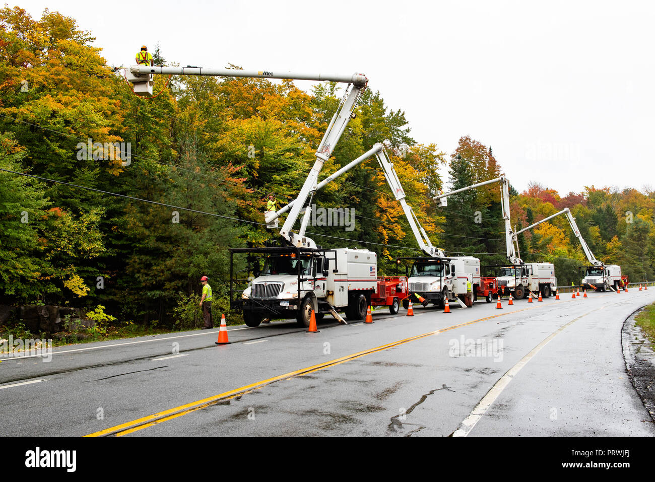 a-fleet-of-service-vehicles-gathered-in-the-adirondacks-mountains-ny-usa-trimming-trees-and-branches-away-from-power-lines-PRWJFJ.jpg