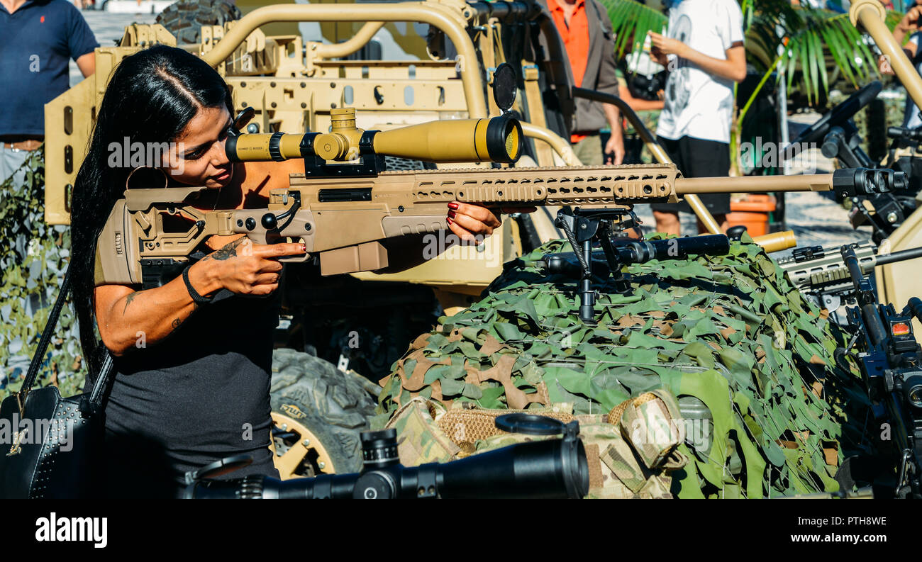 young-beautiful-feminine-civilian-with-handbag-and-tattoos-aiming-using-a-high-tech-army-sniper-rifle-PTH8WE.jpg
