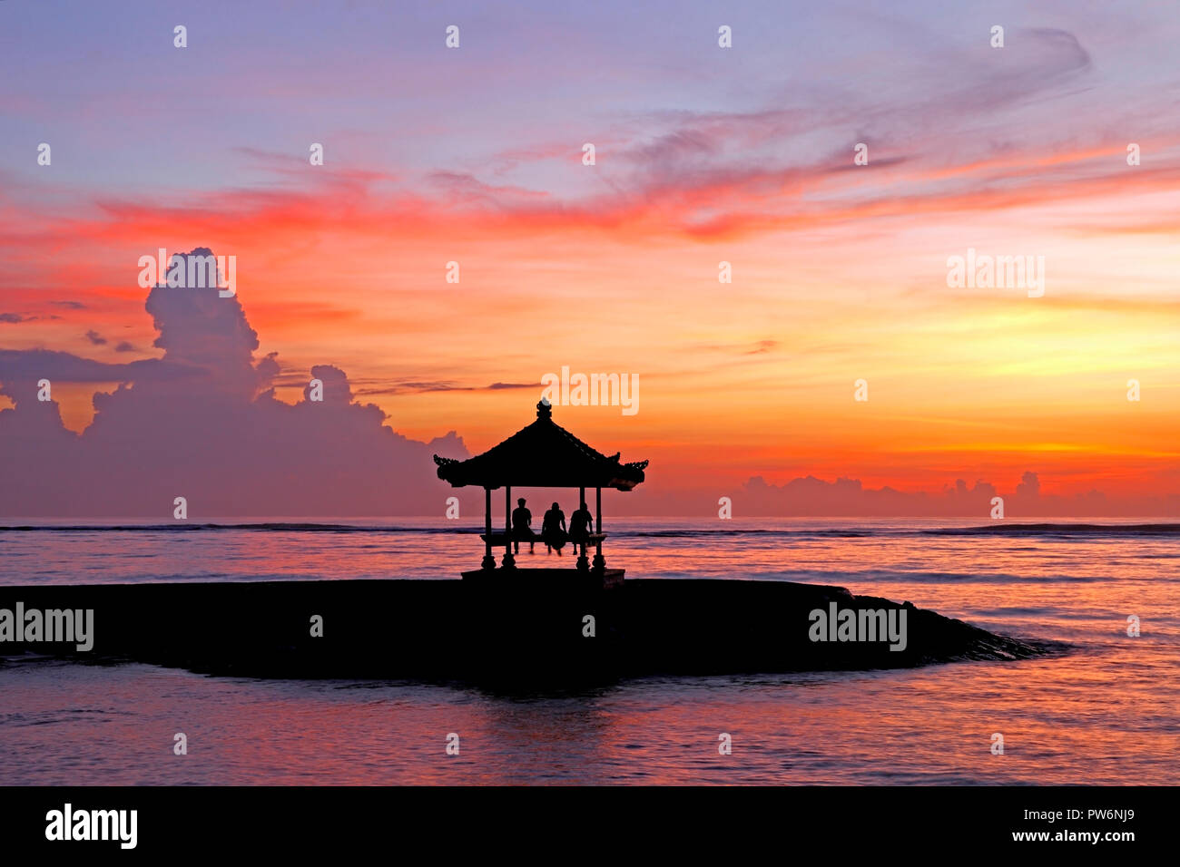 three-people-sitting-in-a-balinese-pagoda-on-sanur-beach-at-sunrise-sanur-beach-bali-indonesia-PW6NJ9.jpg